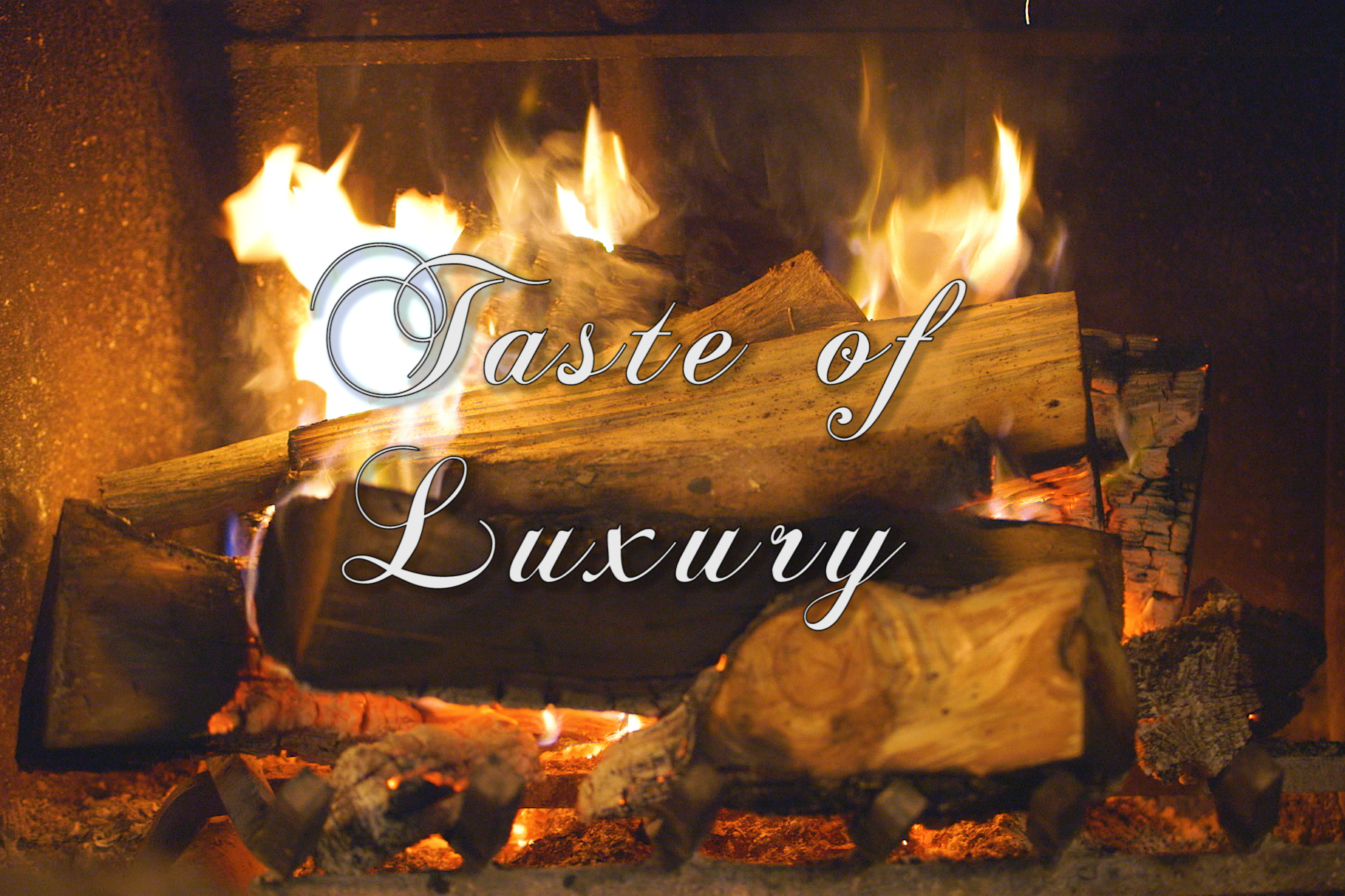 """The words """"Taste of Luxury"""" in white script front superimposed over a close-up photo of a wood fire burning in a fireplace."""