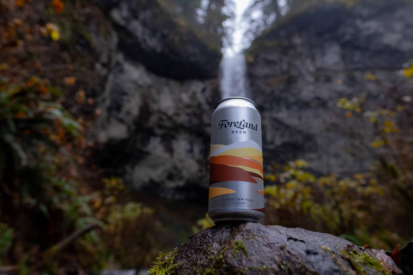 A beer can sits on a rock in front of a waterfall