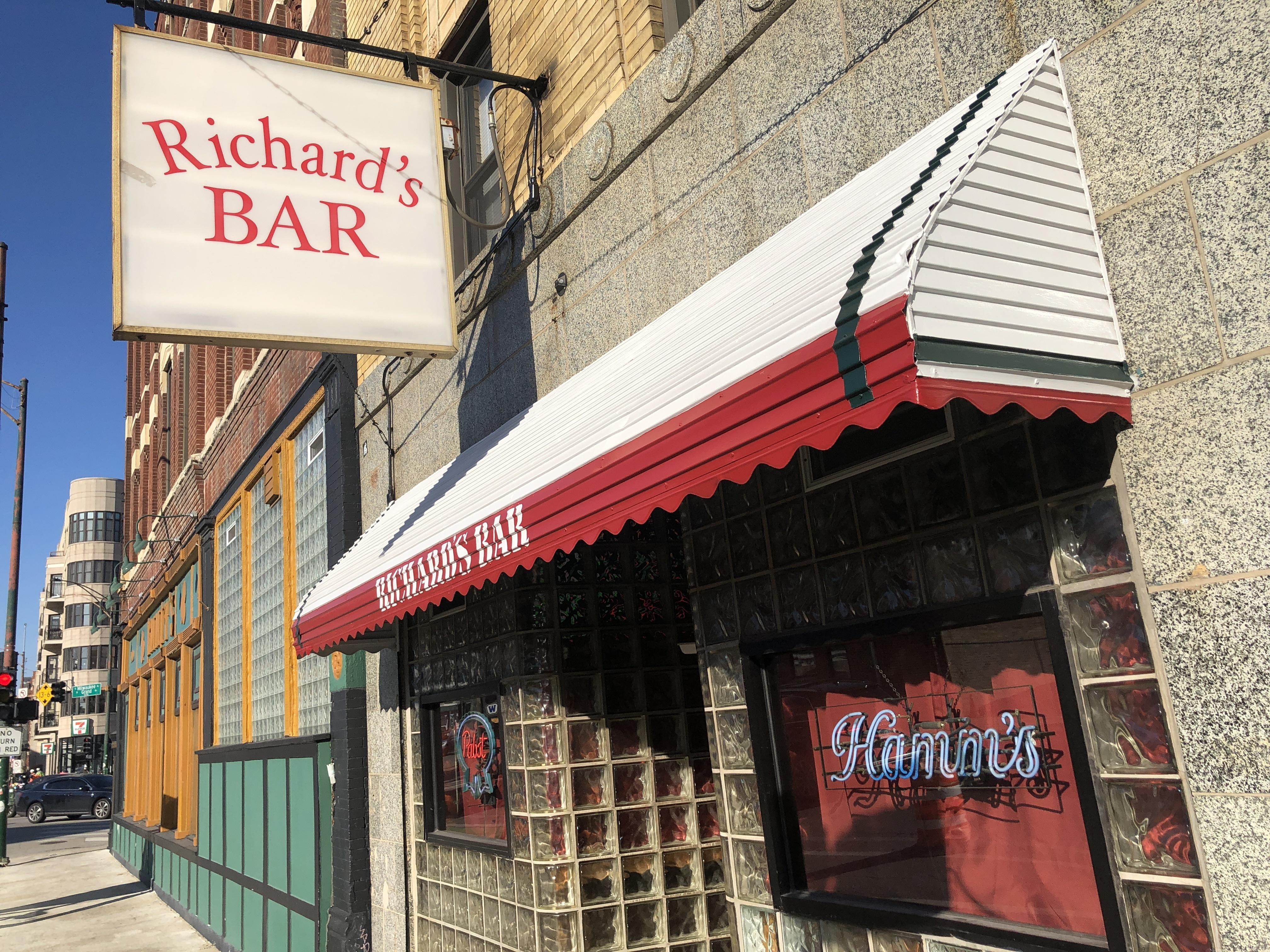 """A red and white awning outside a dive bar with a sign that reads """"Richard's Bar."""""""