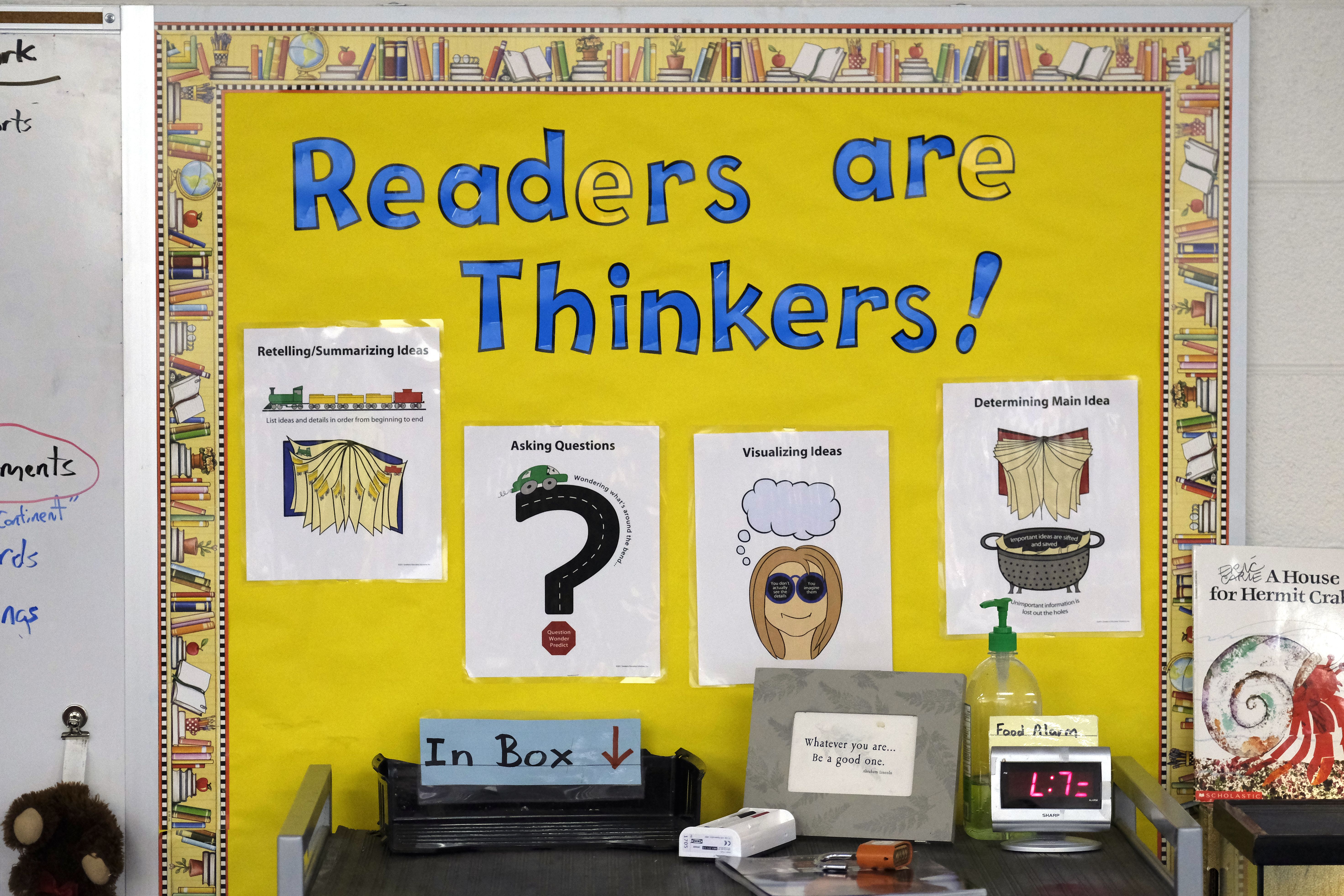 """A yellow wall says """"Readers are Thinkers!"""" in blue lettering. On the wall, are pieces of laminated paper that has pictures and words."""