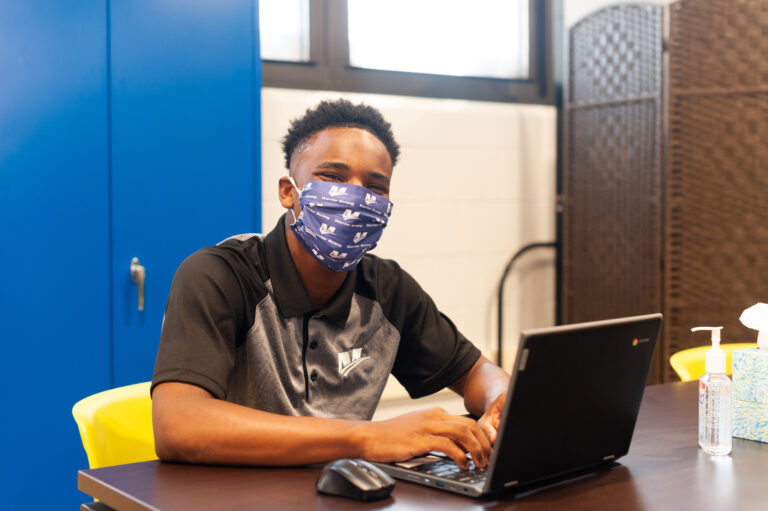 Masked student sitting at desk