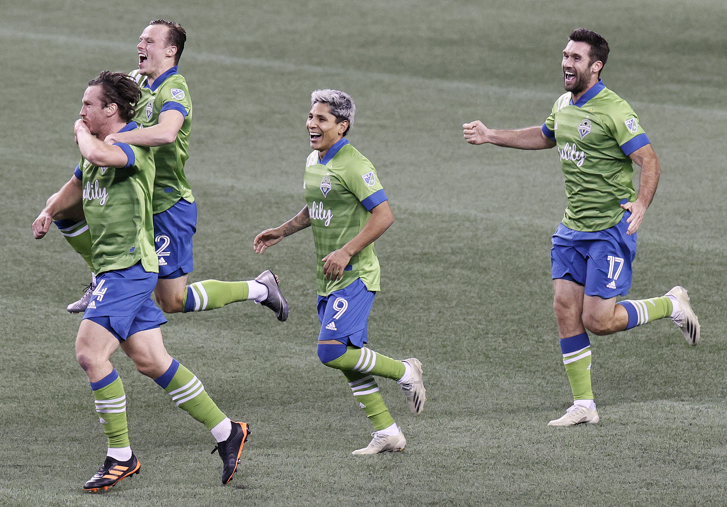 Gustav Svensson of Seattle Sounders celebrates his winning goal with Brad Smith, Raul Ruidiaz, and Will Bruin against the Minnesota United in the second half during the Western Conference Final of the MLS Cup Playoffs at Lumen Field