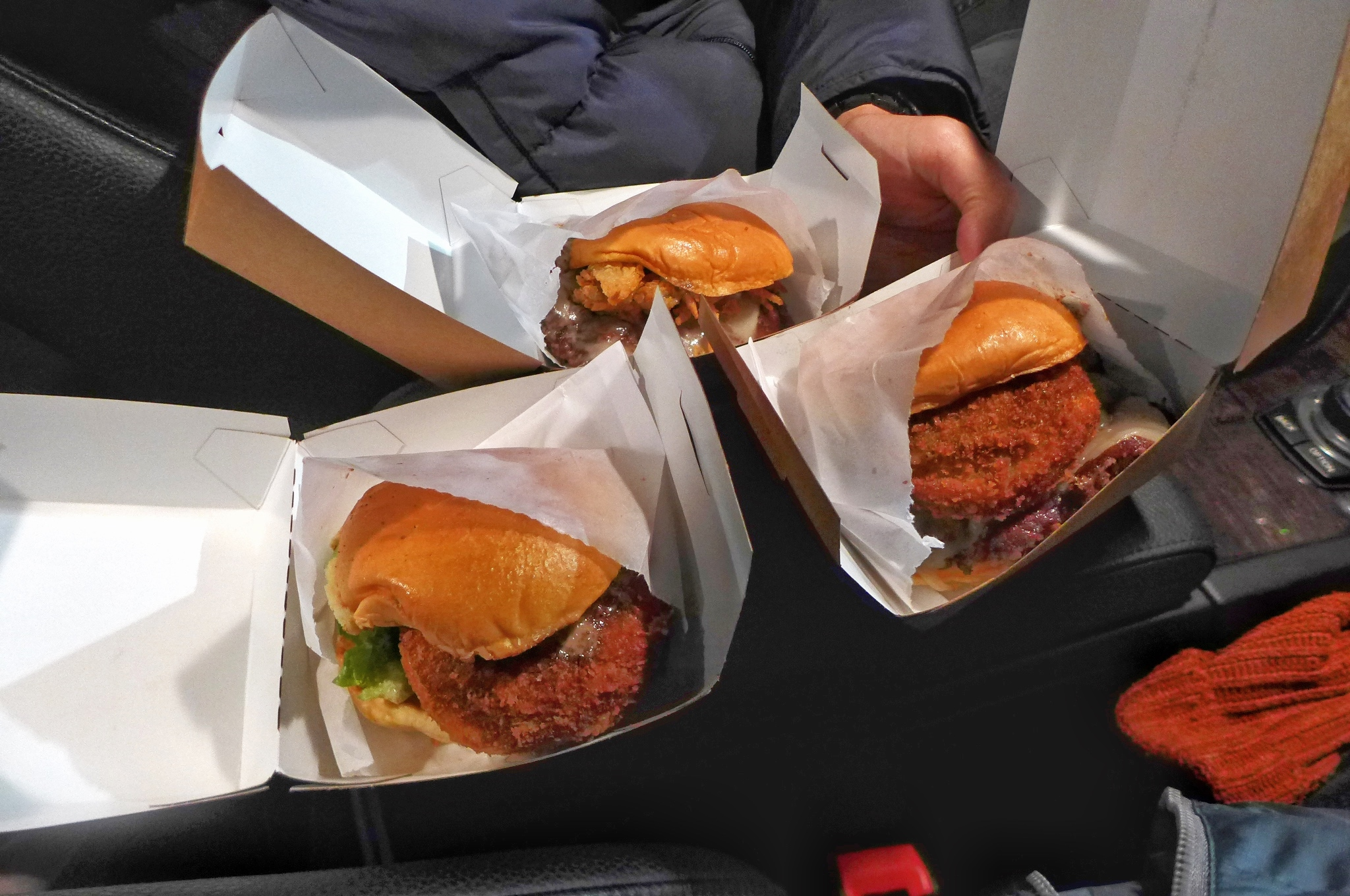 Three burgers in boxes in the darkened interior of a car.