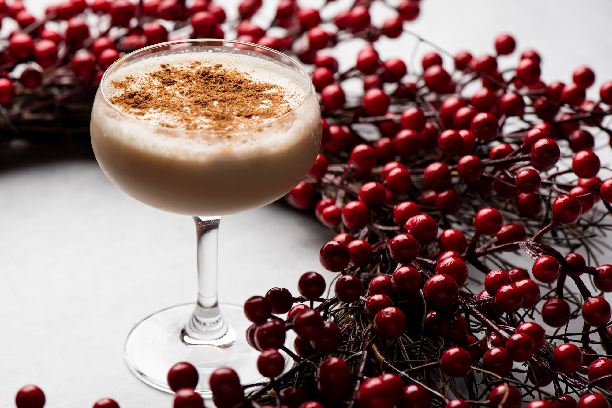 A coupe glass with nutmeg on top of a foamy cocktail for the holidays.