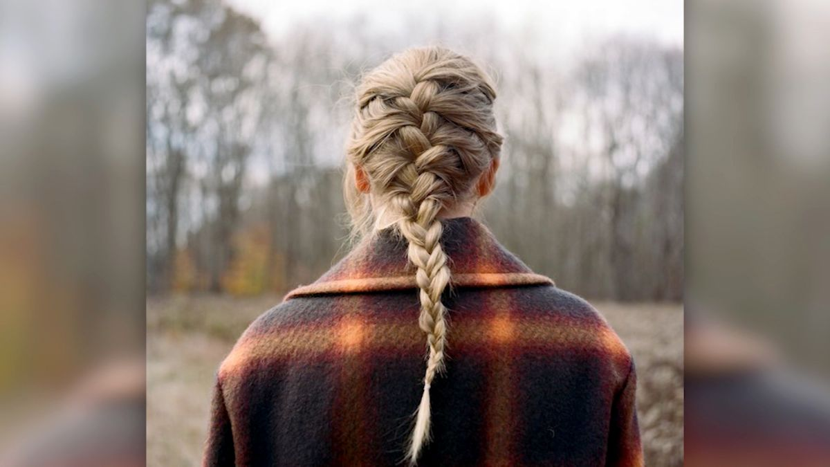 Swift stands with her back to the camera, hair in a French braid
