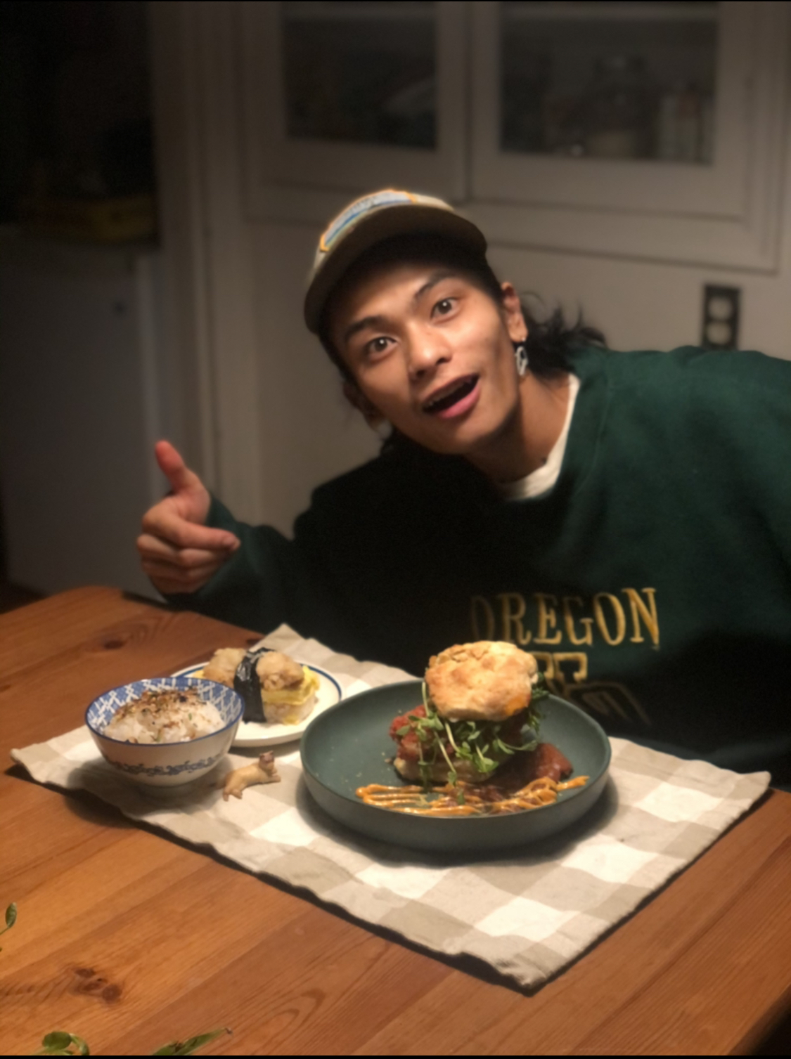 A young man in a hat and sweatshirt points and poses with a fried chicken sandwich