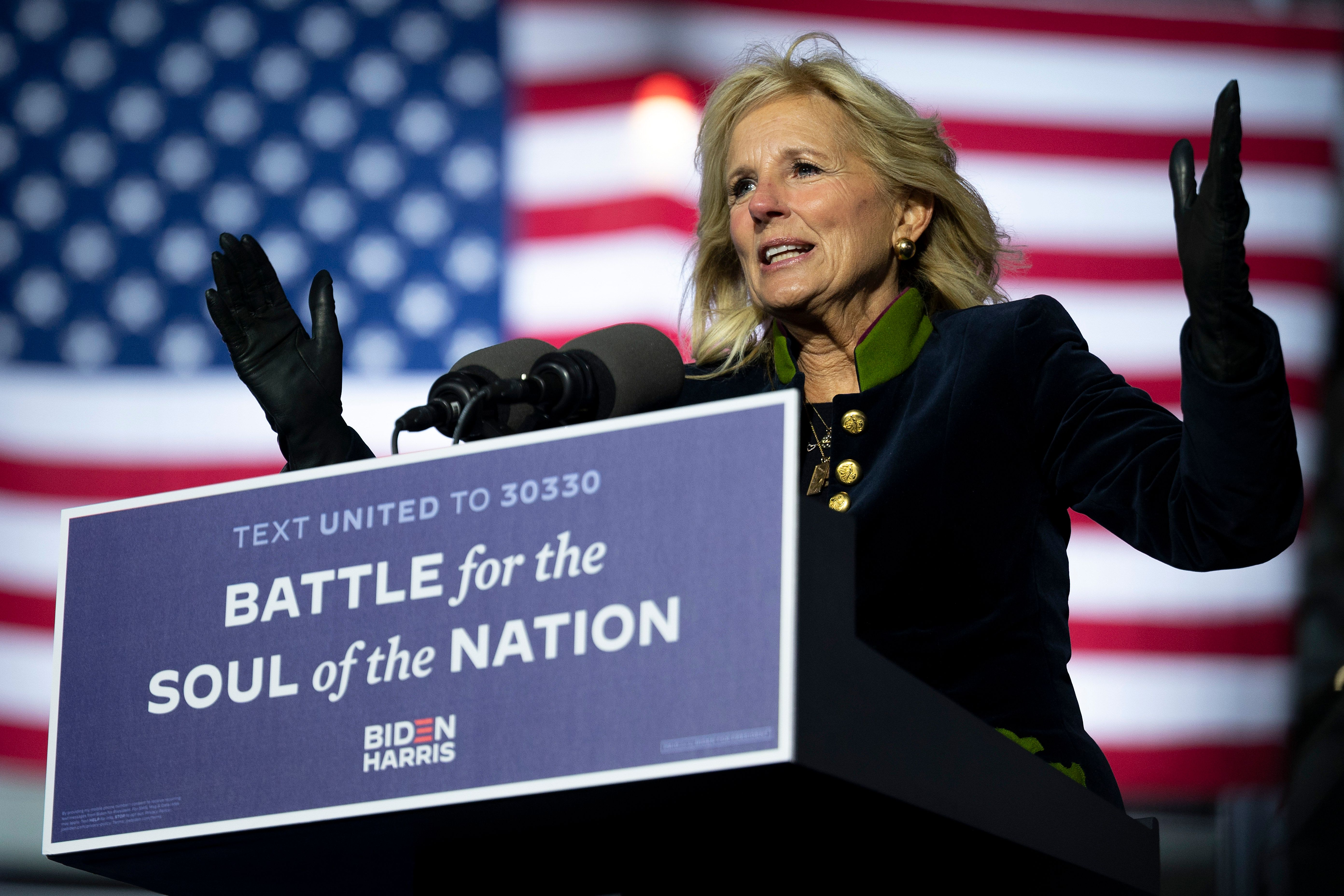 Biden, in a dark blue jacket with a green collar and gold buttons, speaks outdoors in front of a US flag. She is lit by spotlight, and is gesturing broadly with her arms.