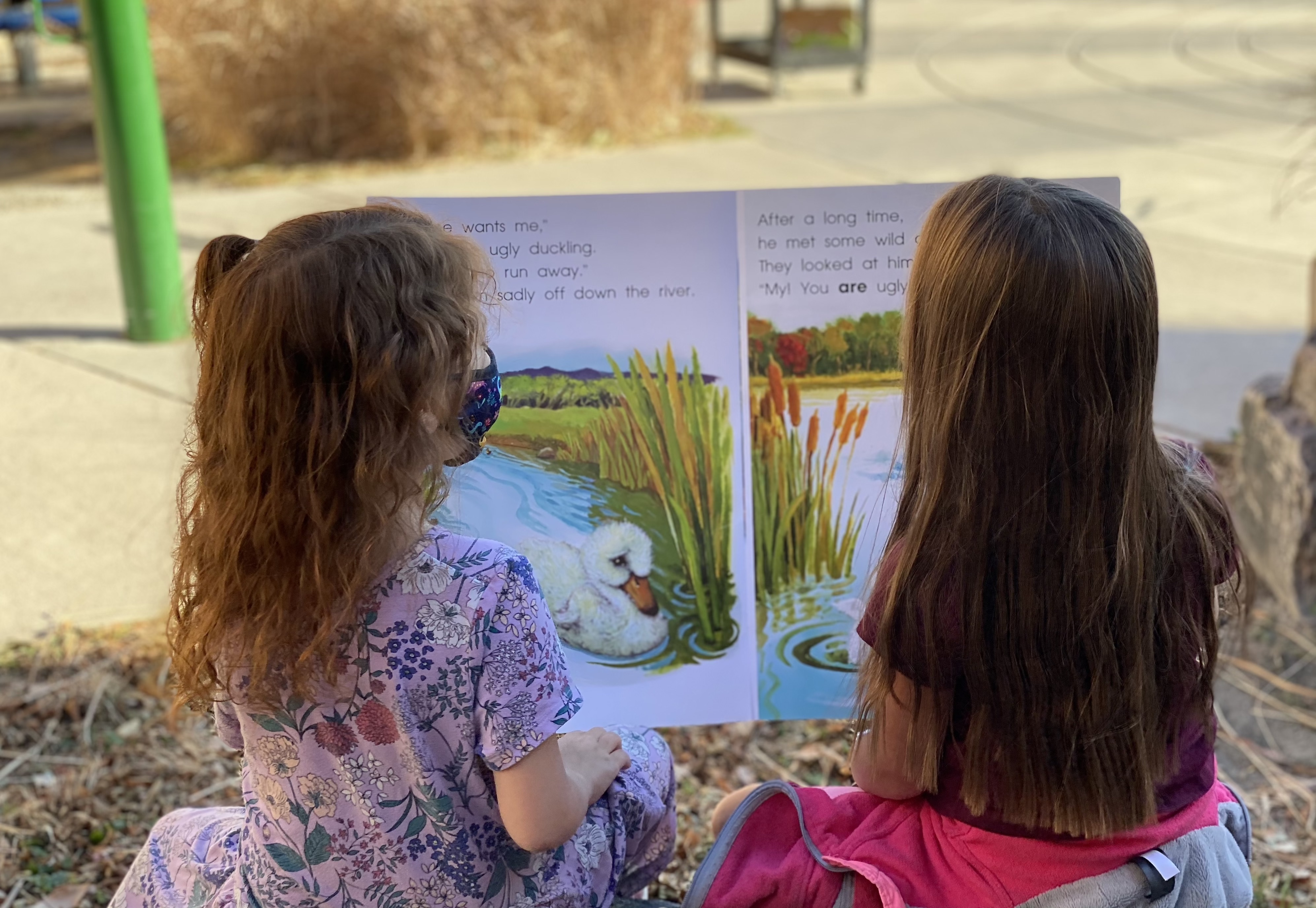 Two first grade girls read a large book outside.