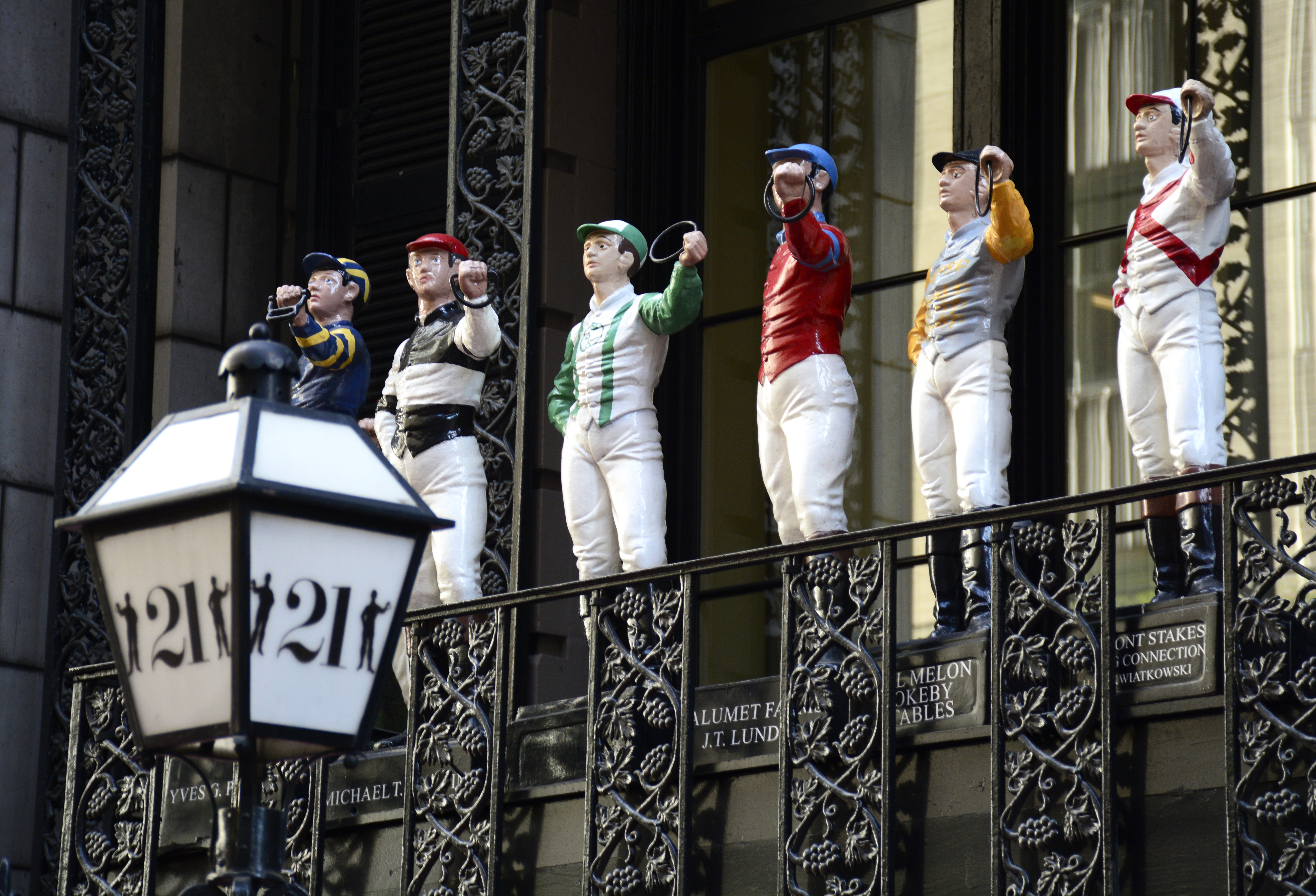 The 21 Club in Midtown Manhattan, a former prohibition-era speakeasy, features a colorful collection of small painted cast iron lawn jockey statues which adorn the balcony above the entrance.