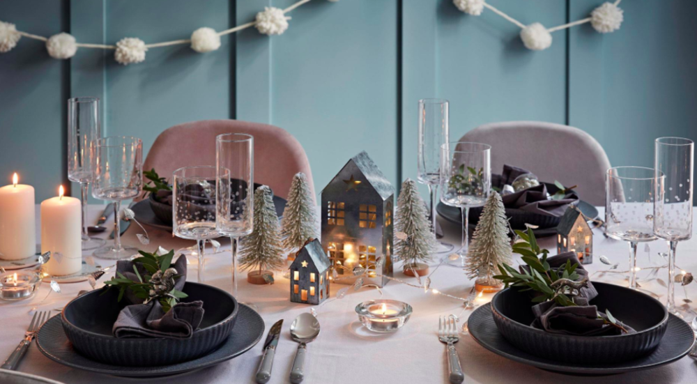A table inside Stewart's set with black plates on a white tablecloth. There are candles and small houses next to bottle brush green trees dusted with fake snow