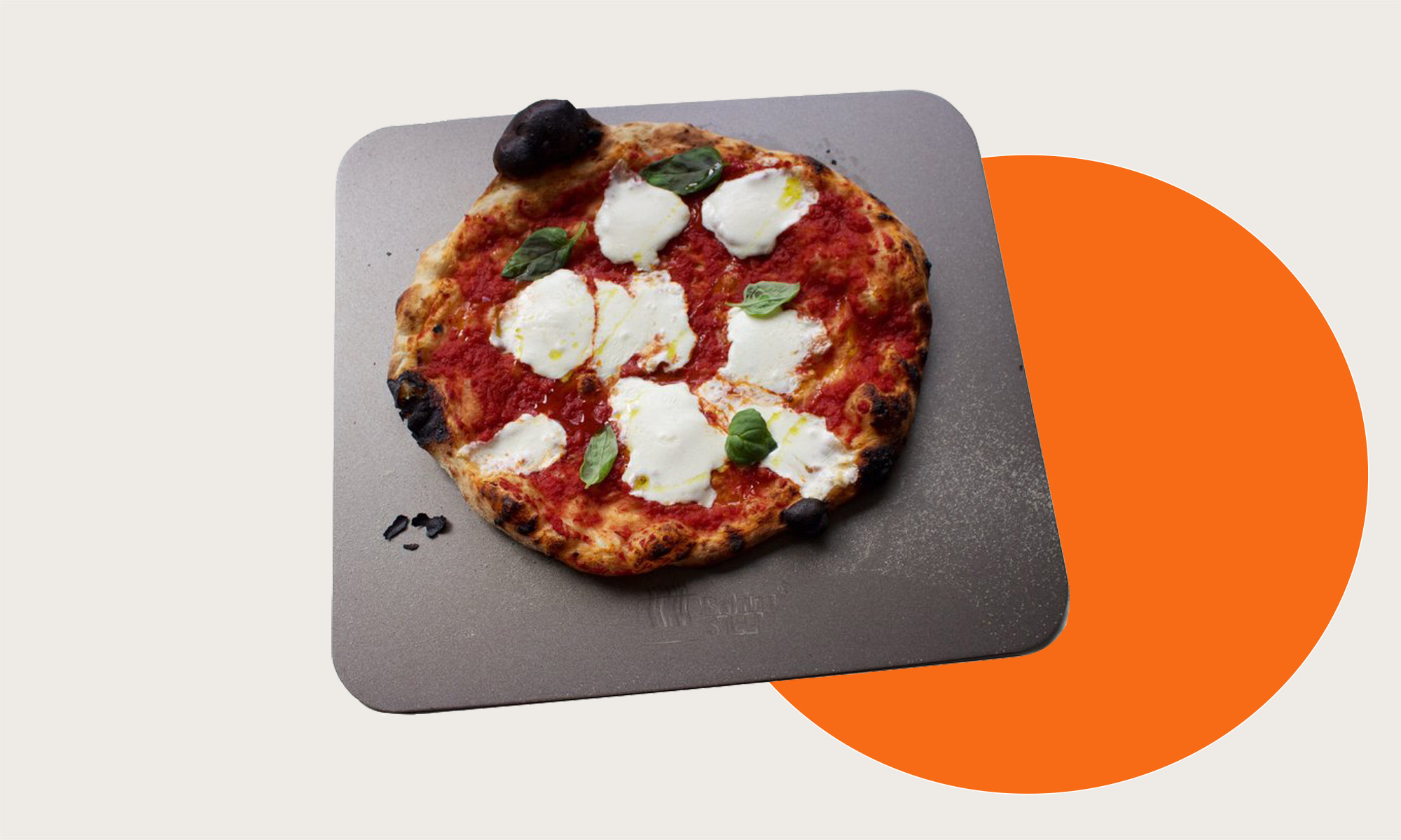 A baking steel with a margherita pizza