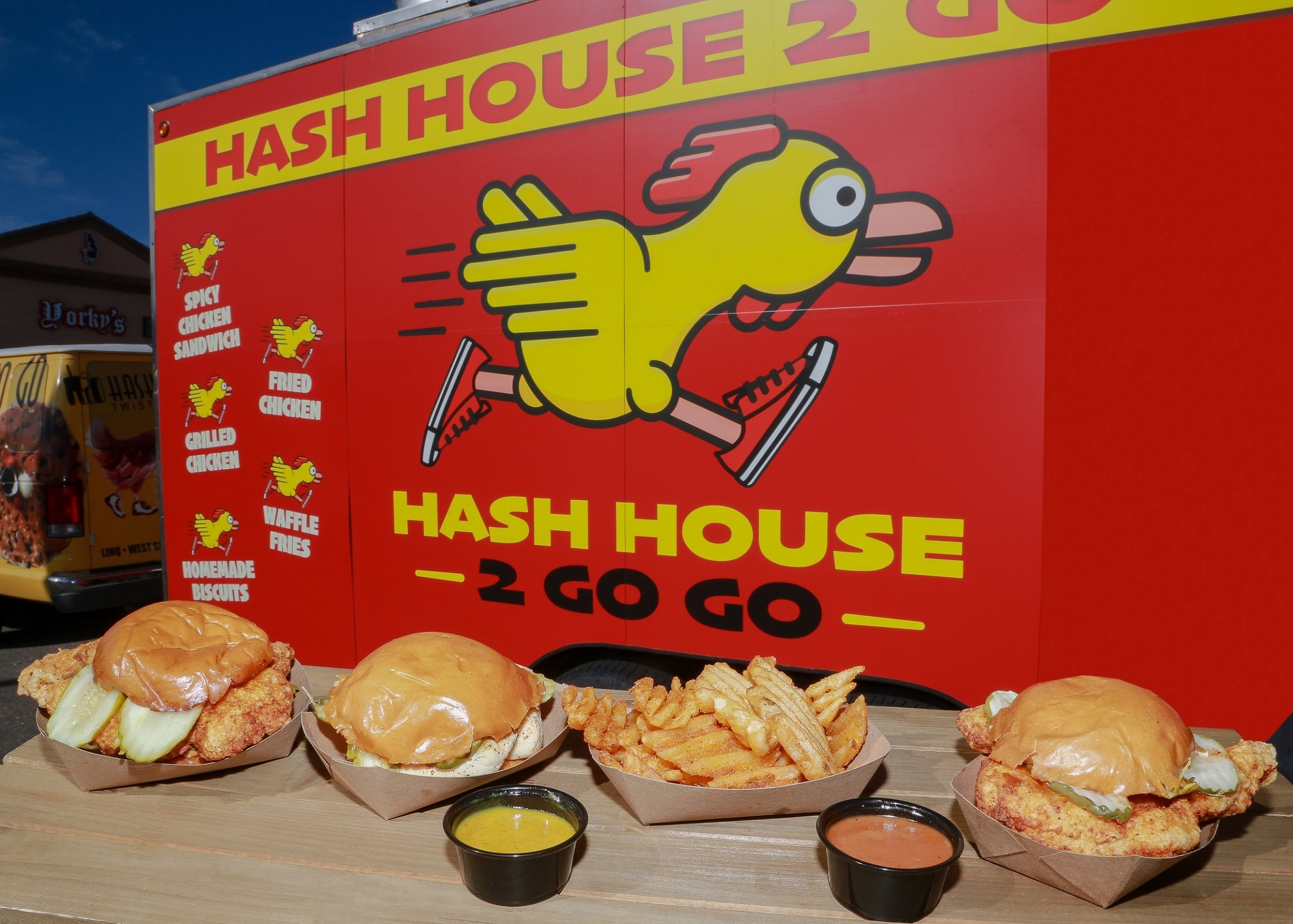 A food truck with a cheeky chicken on the side and four sandwiches on a table in front of it
