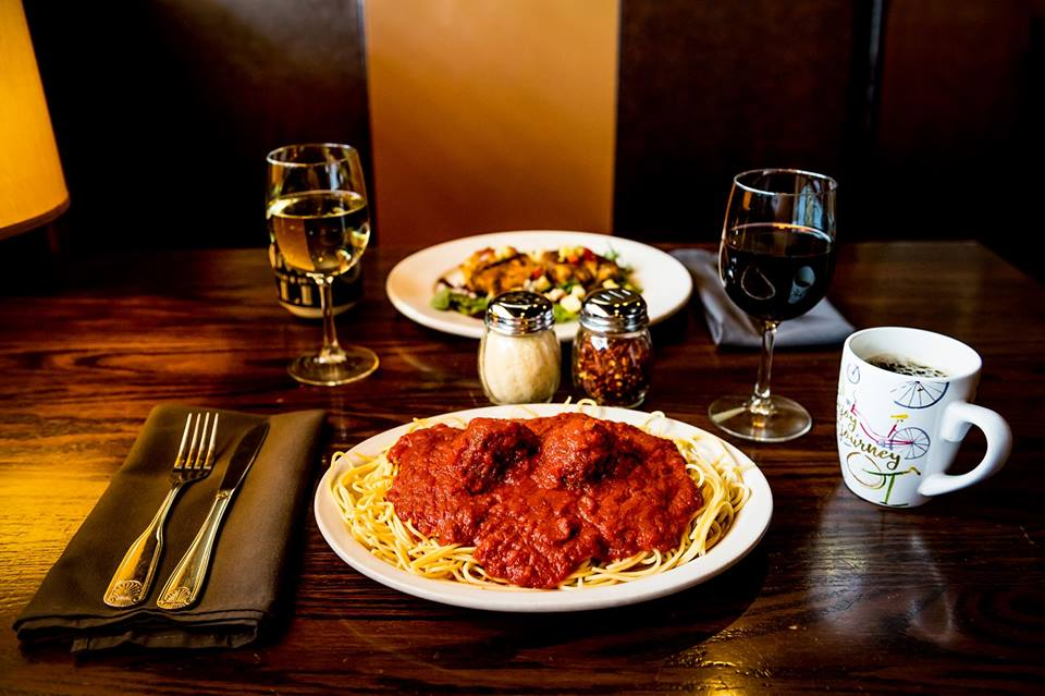 A table set with a plate of spaghetti and meatballs