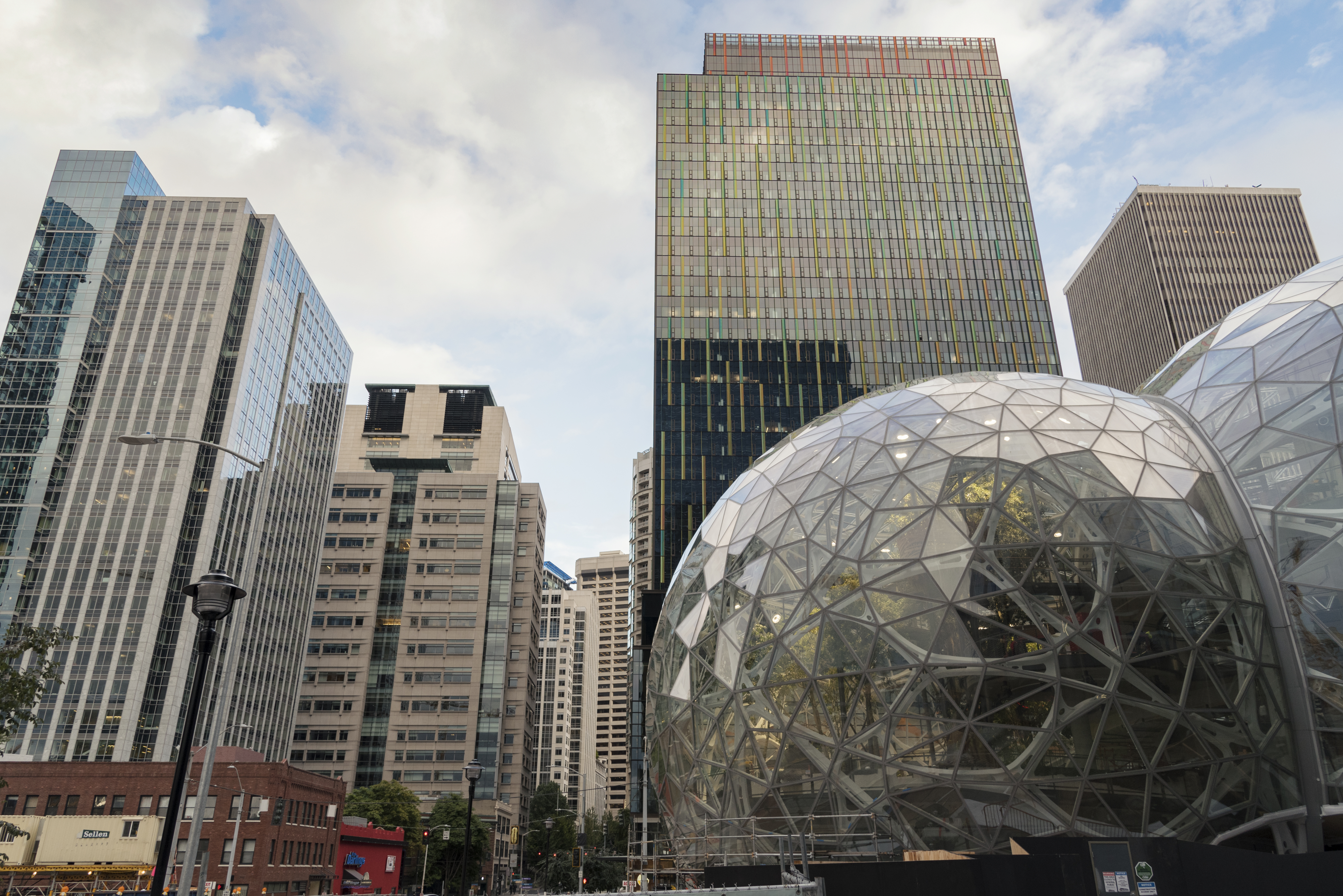 A view of Amazon's downtown campus on a cloudy day, with a main office building and the Spheres shown at the right