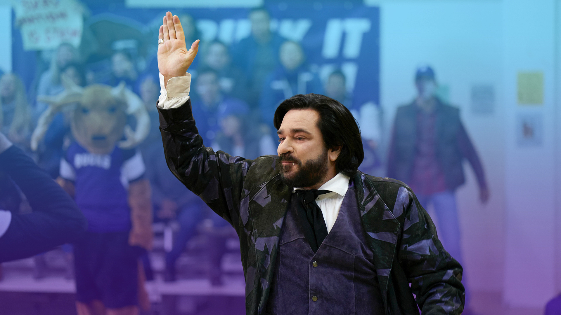 """A scene from """"What We Do in the Shadows"""" TV show: A modern day vampire from the raises his hand to a sports crowd"""