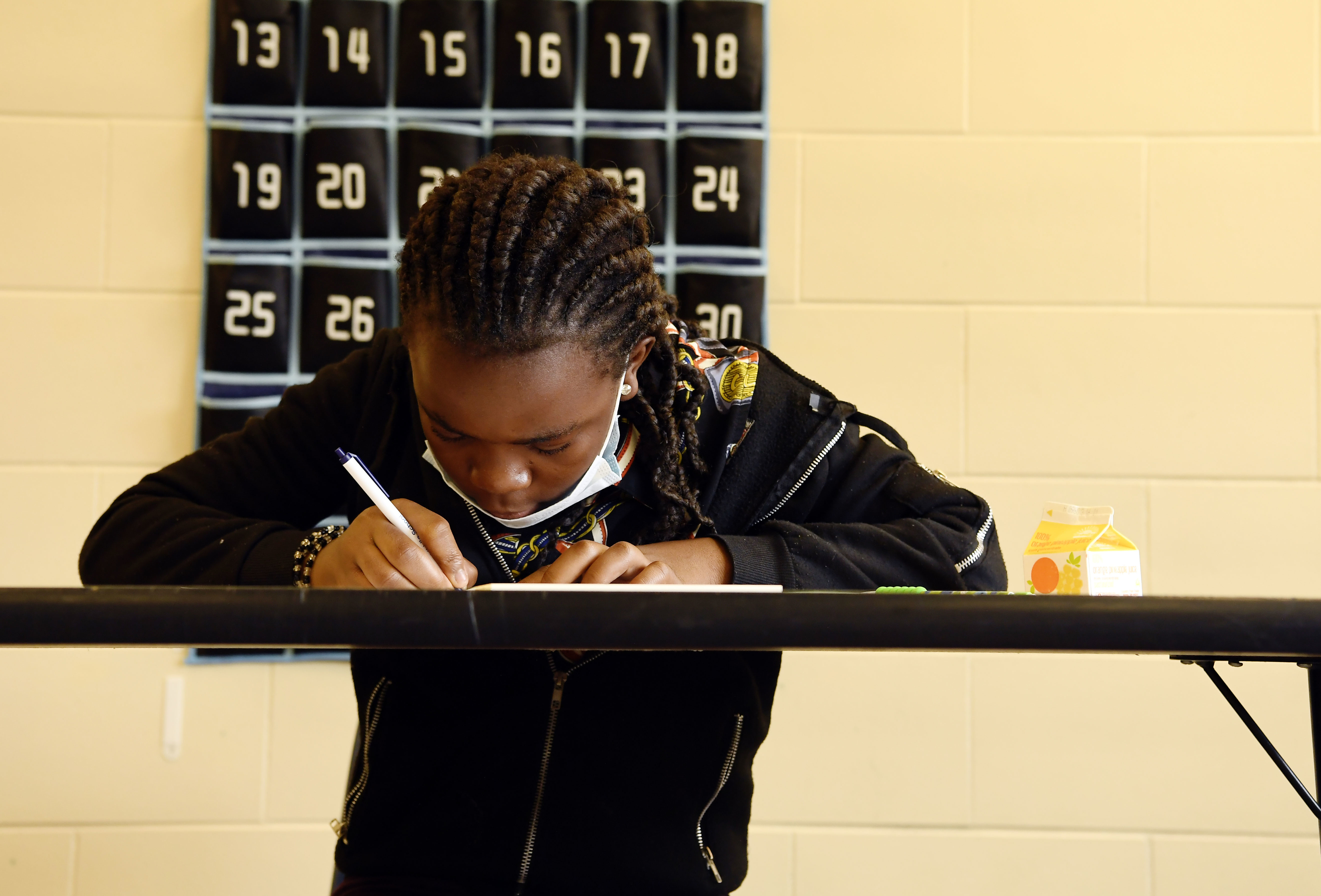 Student writing at a table in a classroom.