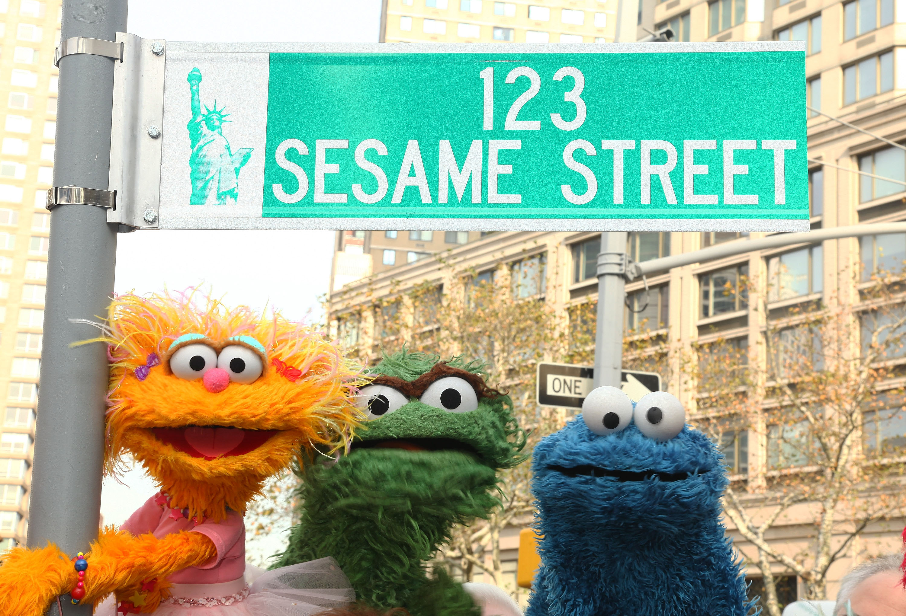 """Sesame Street characters pose under a """"123 Sesame Street"""" sign at the """"Sesame Street"""" 40th Anniversary temporary street renaming in Dante Park on November 9, 2009, in New York City."""