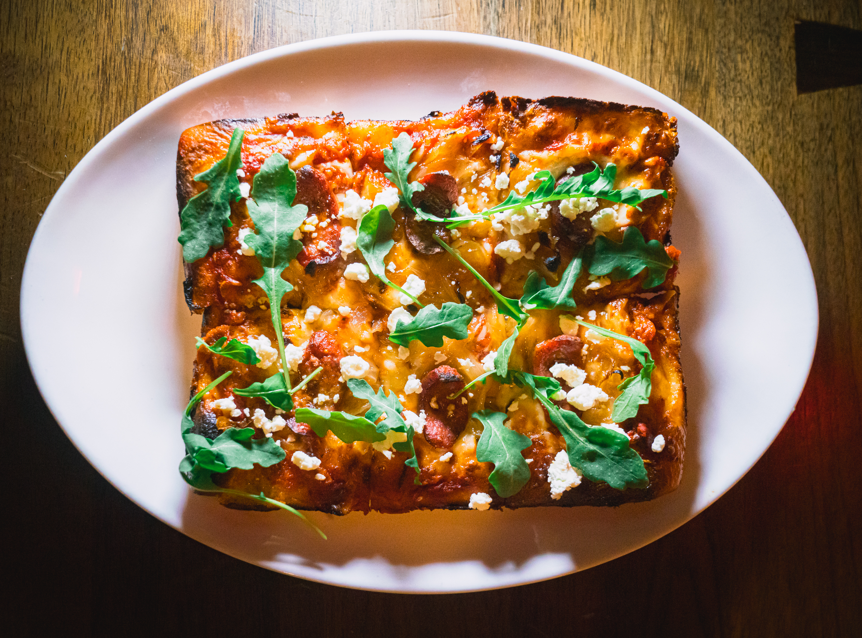 Get Social's Half Smoked Goat pizza gets topped with half-smoke slices, caramelized onion, goat cheese, and arugula