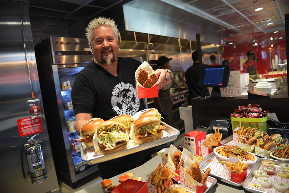 Celebrity chef Guy Fieri holding a plate of sandwiches at his Chicken Guy! restaurant inside the Aventura Mall, Miami.