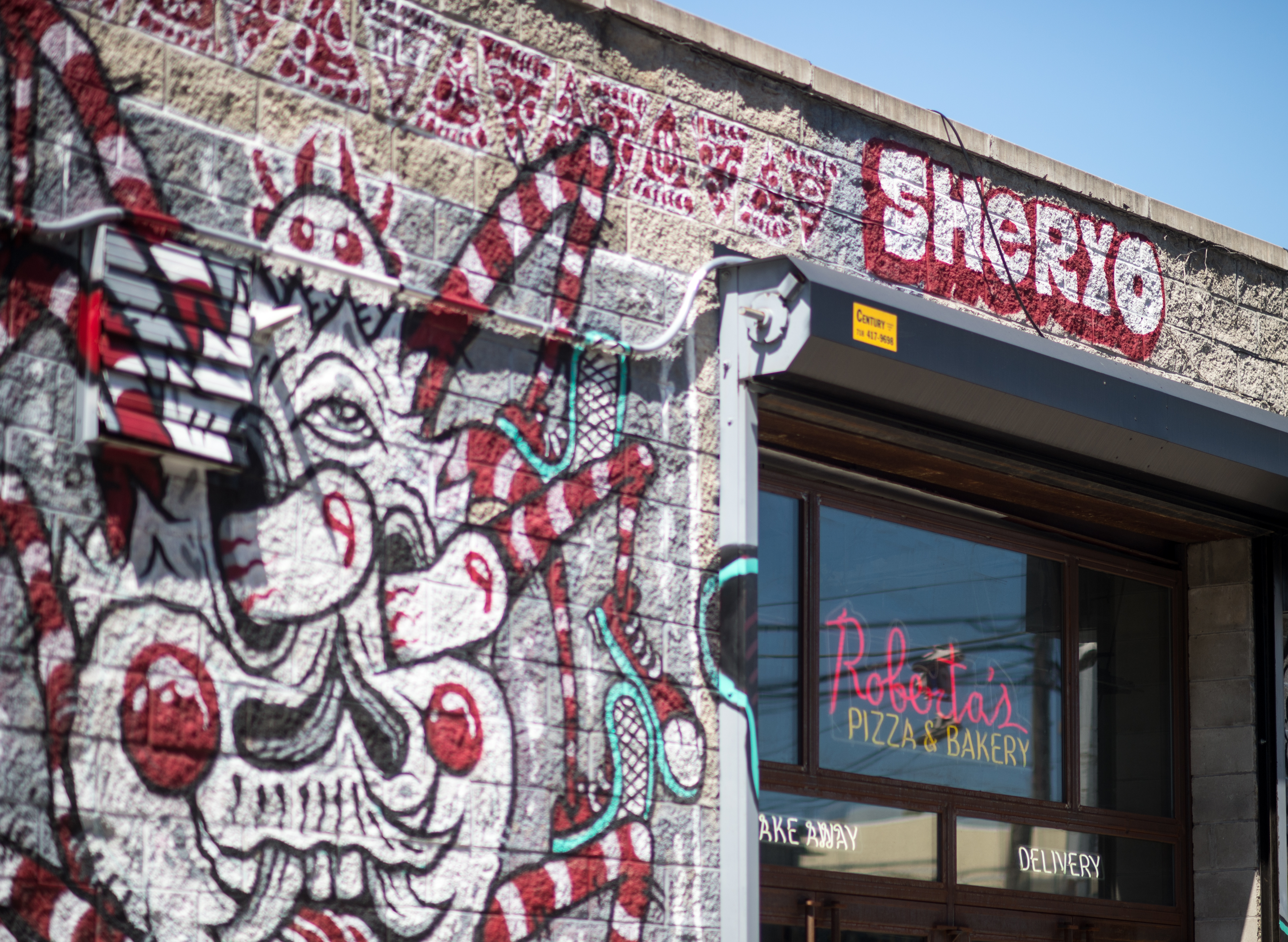 """A graffitied exterior of a building with a """"Roberta's"""" sign hanging in the window"""