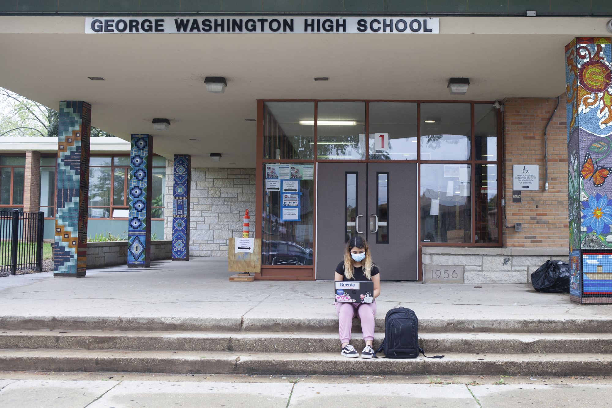 Trinity sitting on steps outside of school with her backpack and laptop.