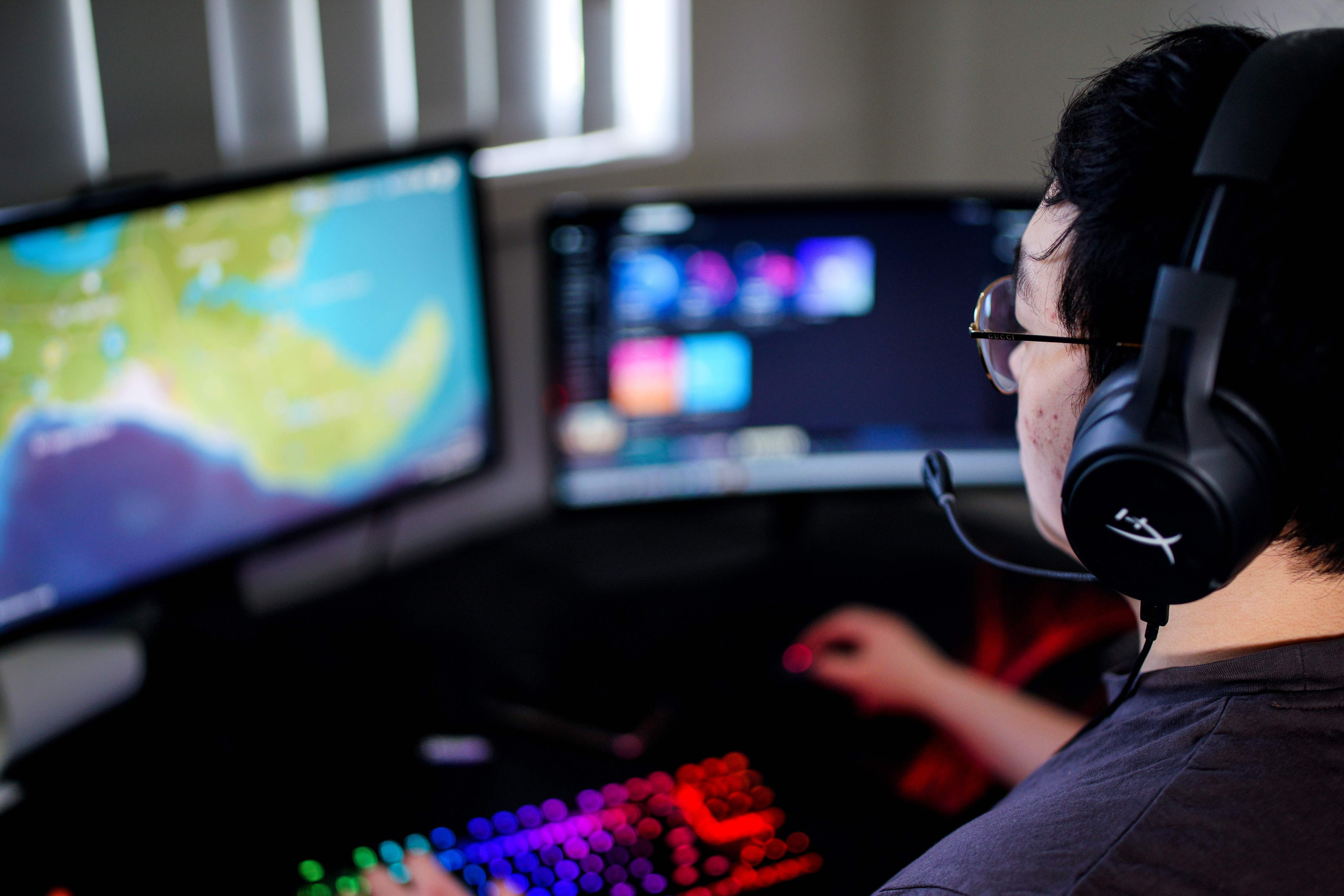 "This picture taken on November 13, 2020 shows Dragon Gou, who played under the moniker ""Dragku"" for the Chiefs eSports Club, playing video games at his home in Sydney. - Despite a global boom, the closure of one of the southern hemisphere's biggest eSports leagues has left its players in Australia and across Oceania facing an uncertain future. Photo by ANDREW LEESON/AFP via Getty Images) ORG XMIT: 0"