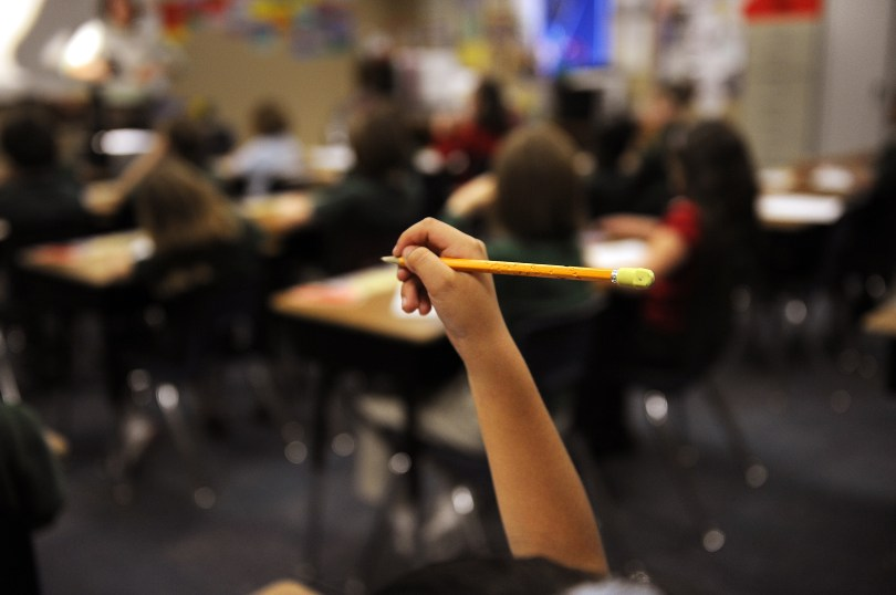 A raised hand holds a pencil. In the background, students sit at desks in a classroom.