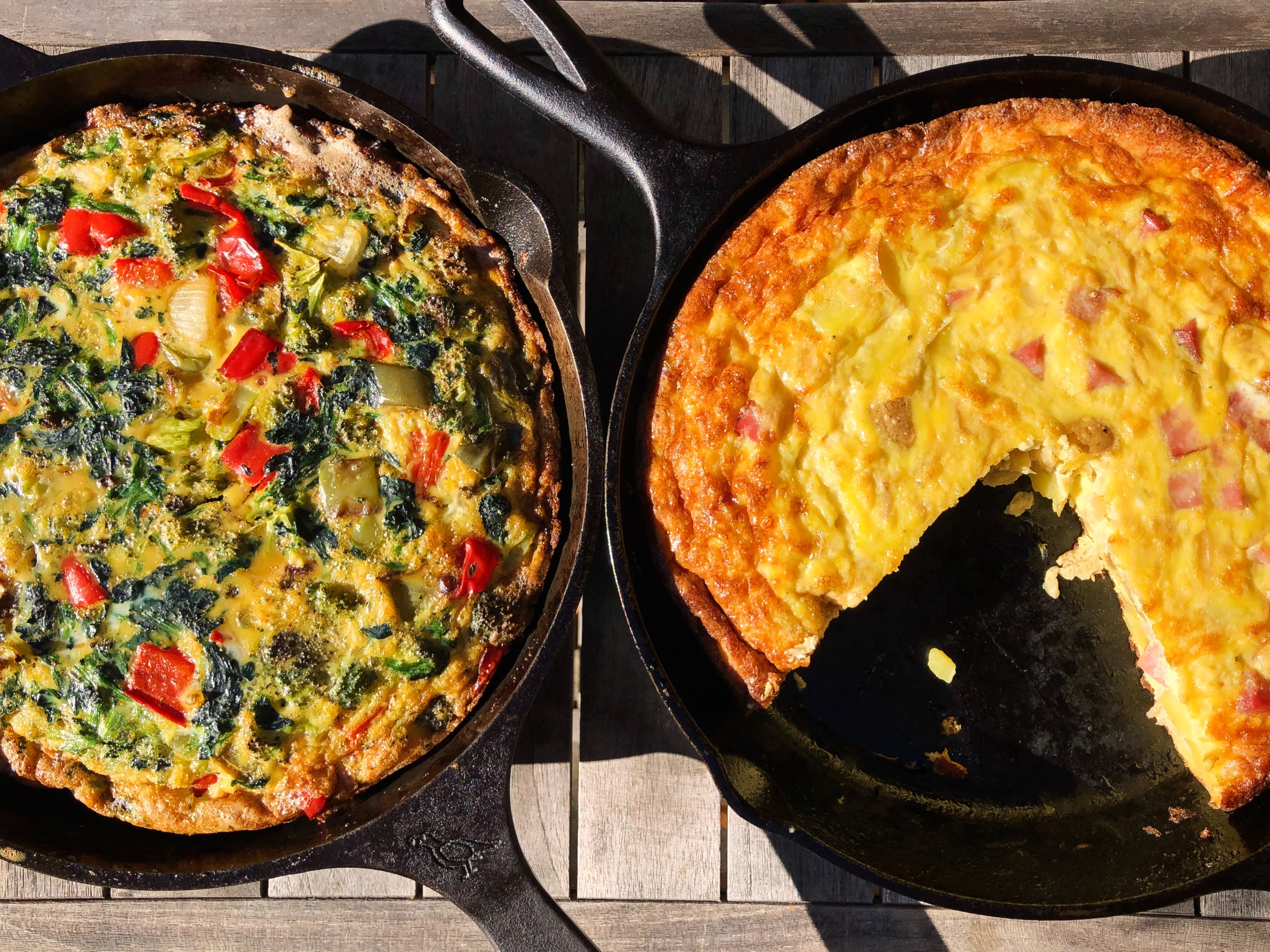 Overhead photo shows two frittatas in cast iron pans, one of them with a slice missing.