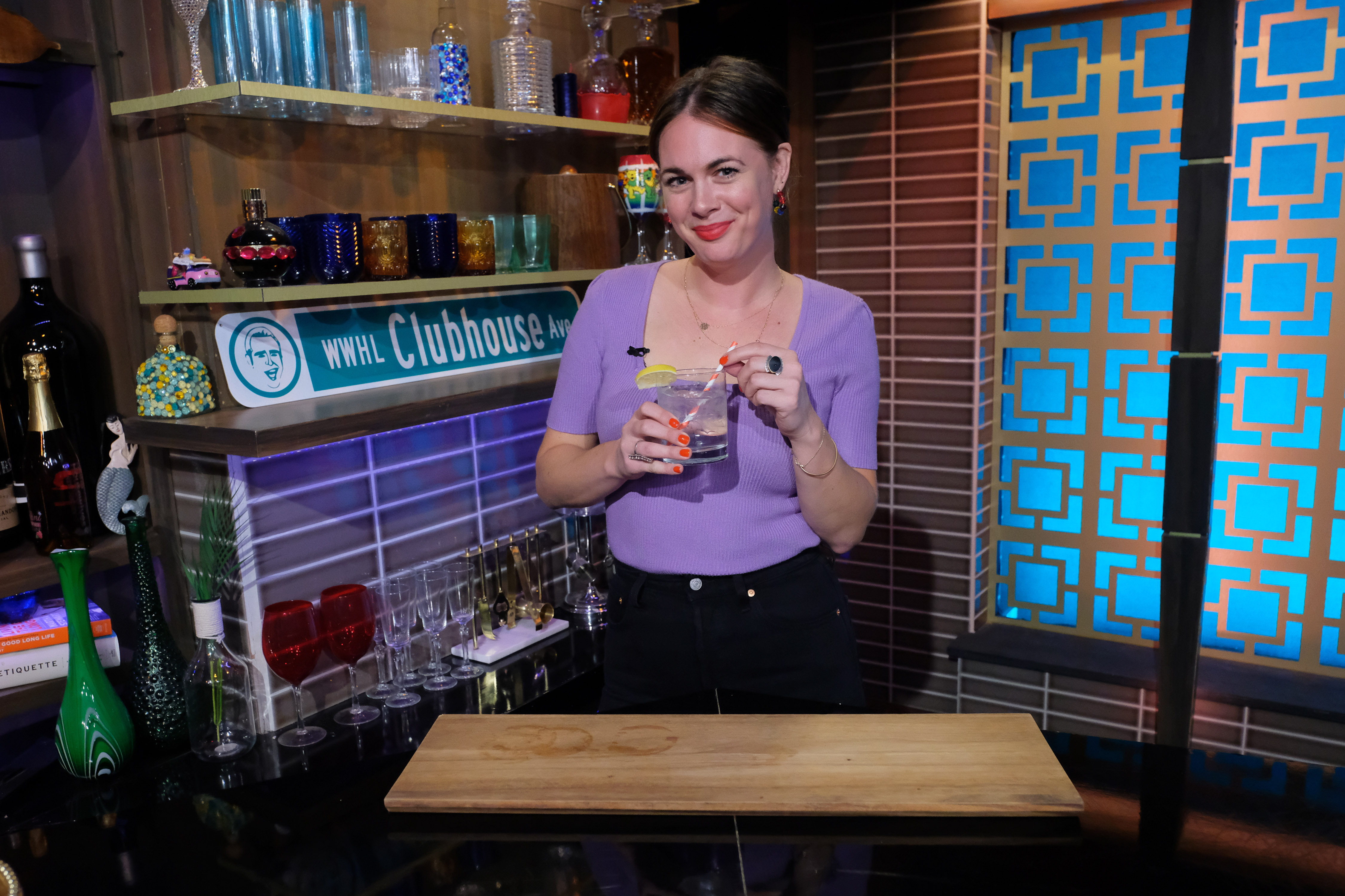Alison Roman holding a drink on a show set.