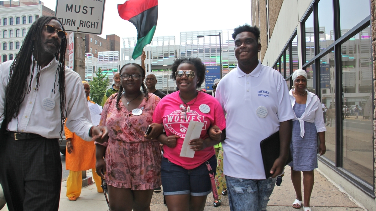 Cheyney students (from right) Shaquille Harrison, Nyrie Watson and Shaneka Briggs link arms as they make their way to Gov. Tom Wolf's Philadelphia office on Eighth Street to deliver a letter demanding funds for the struggling historically black university.