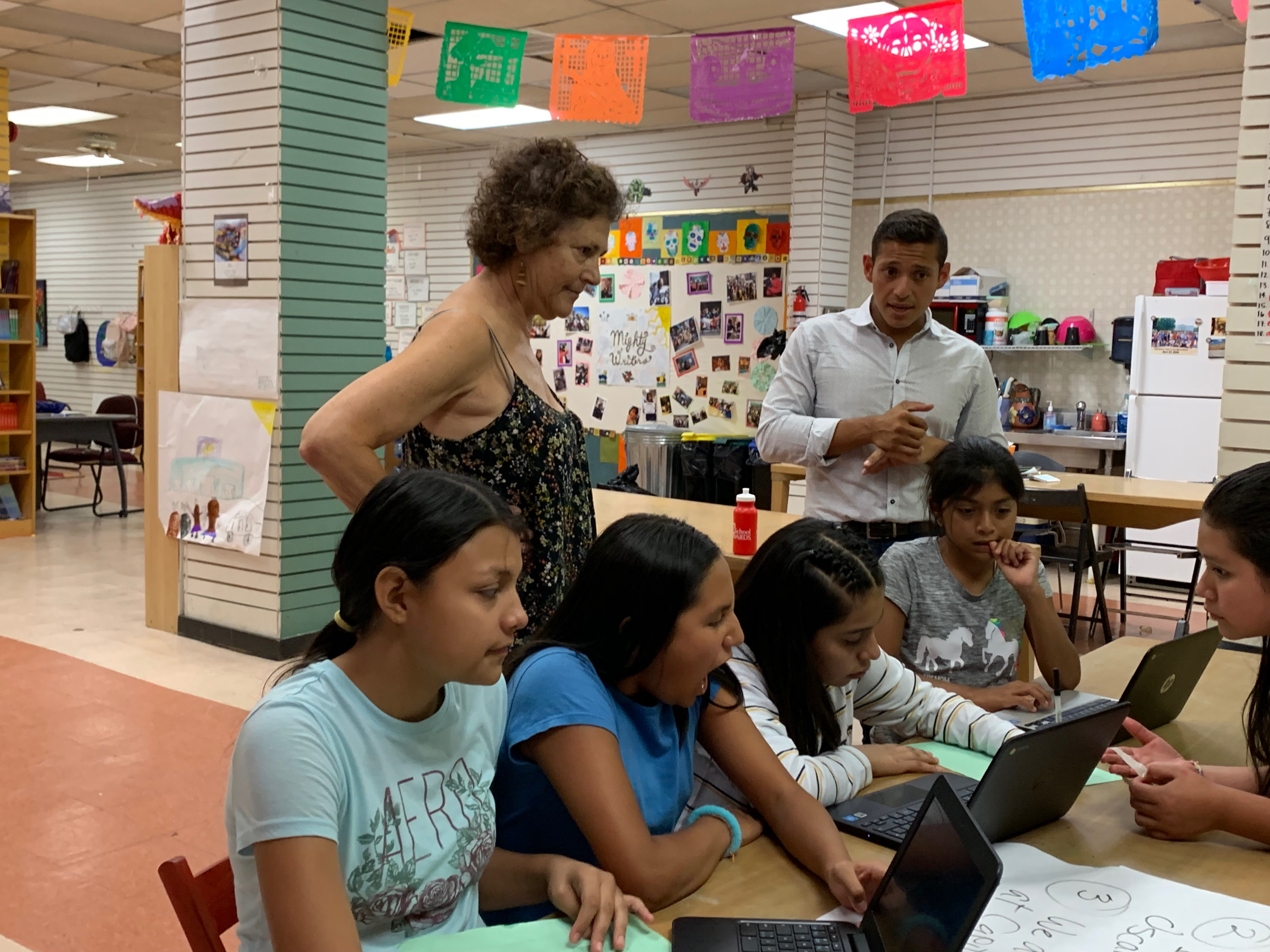 Students work on their writing at the El Futuro site of Mighty Writers with volunteer Sandee Mandel and Telemundo reporter Miguel Martinez-Valle.
