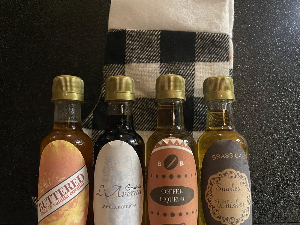 Four tiny bottles of alcohol sit on top of a black and white plaid Christmas stocking