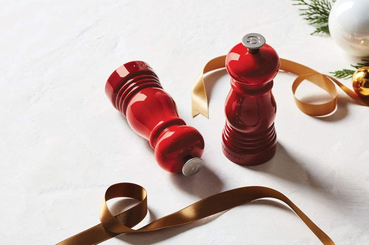 A red salt and pepper shaker and some decorative ribbon