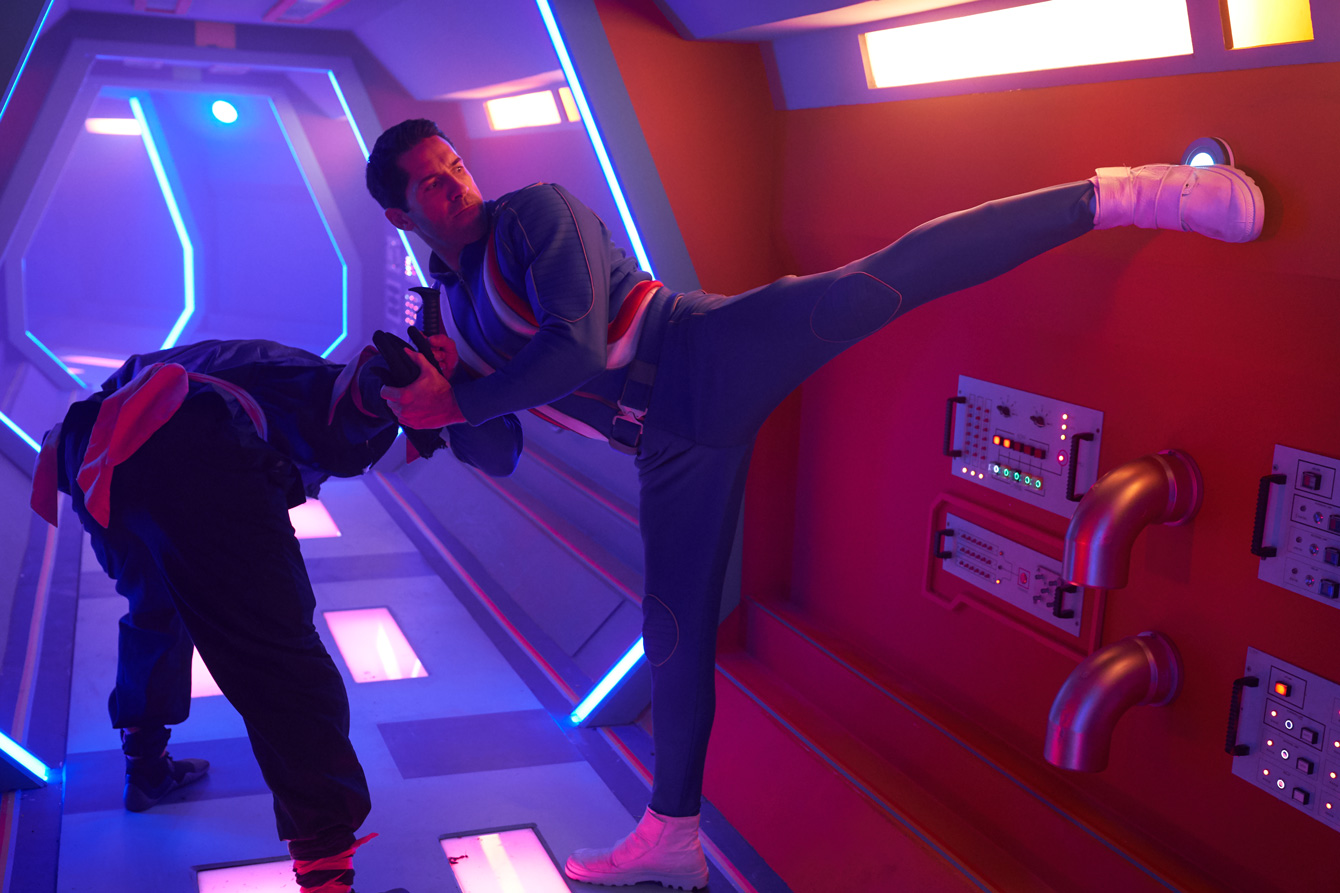 Scott Adkins, in a blue jumpsuit, disables an enemy while kick-activating a button on the wall in Max Cloud