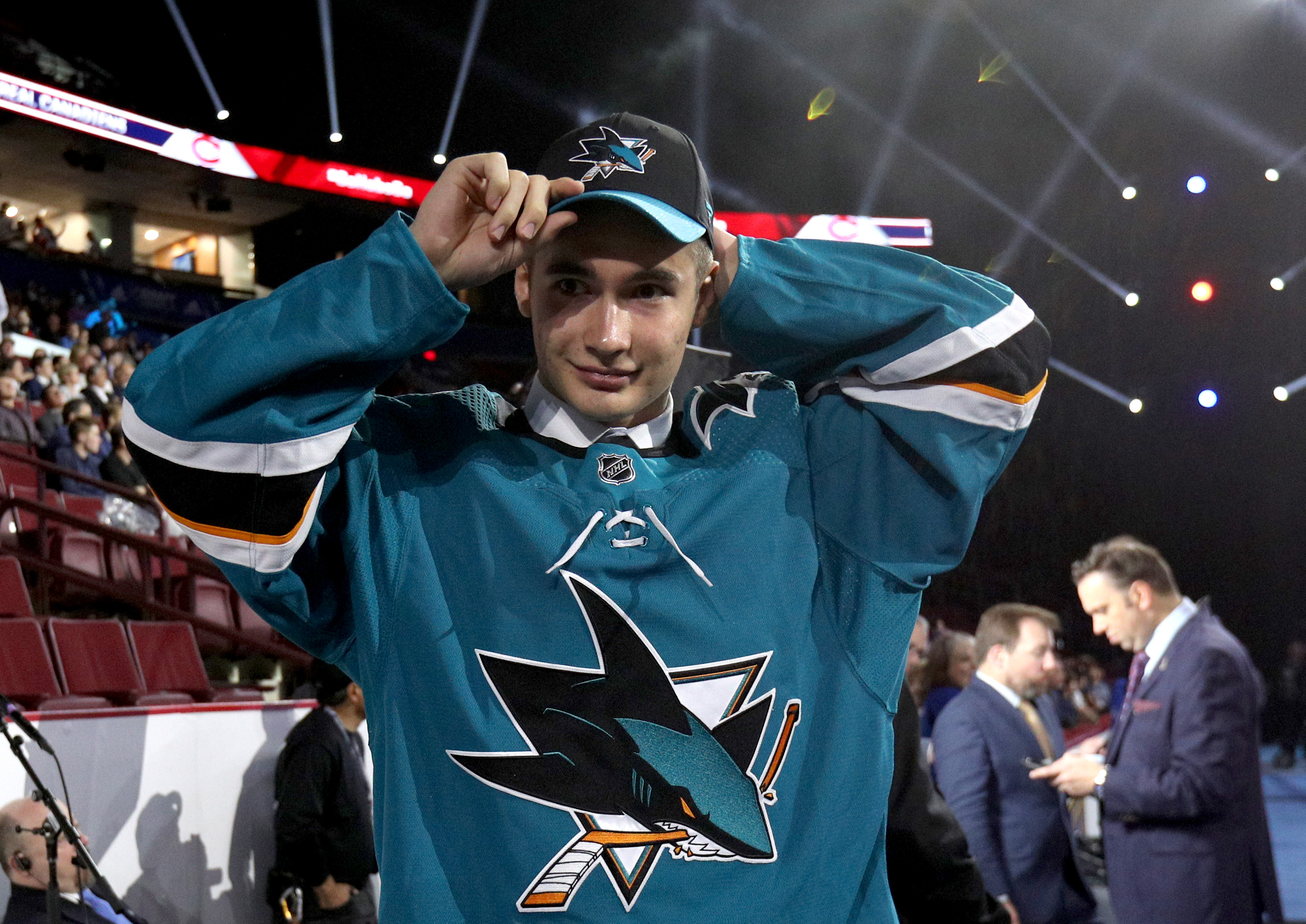 Artemi Kniazev, 48th overall pick of the San Jose Sharks, puts on a team hat during Rounds 2-7 of the 2019 NHL Draft at Rogers Arena on June 22, 2019 in Vancouver, Canada.