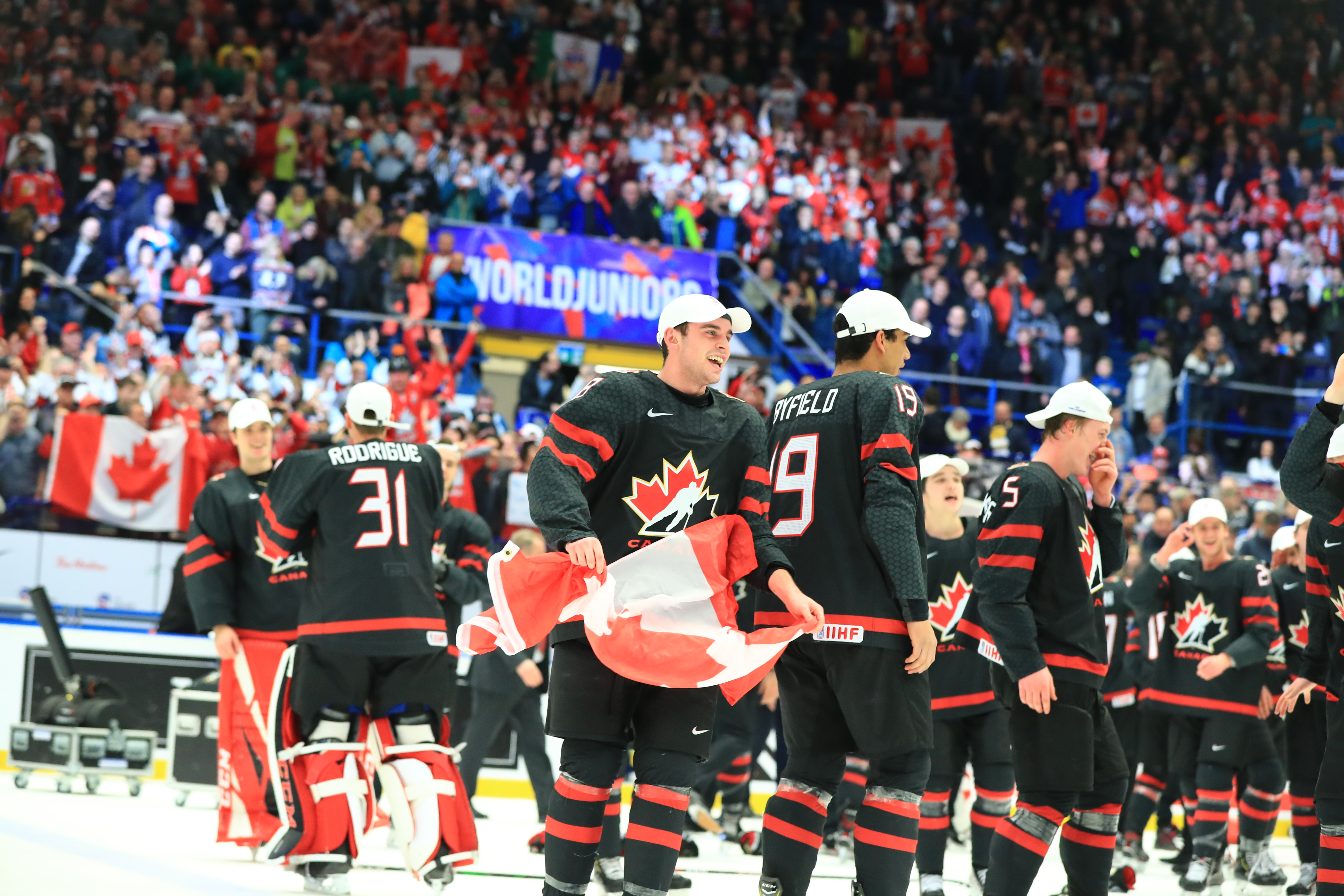 Canadian players Liam Foudy, Quinton Byfield, and Jacob Bernard-Docker (L-R front) celebrate with the trophy after the medal ceremony for the 2020 World Junior Ice Hockey Championship final match between Canada and Russia at Ostravar Arena; Canada won 4-3.