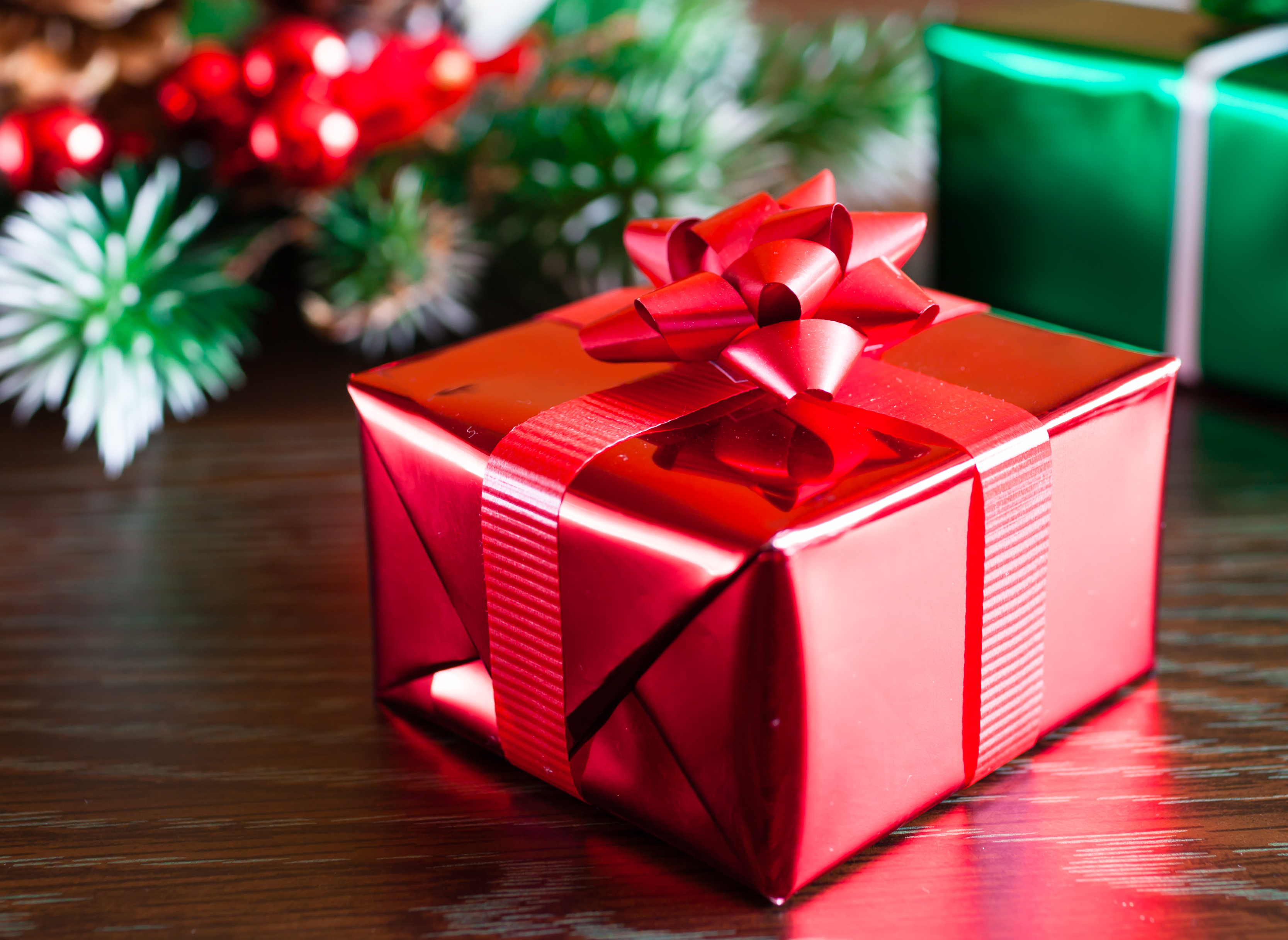 A gift neatly wrapped in shiny red paper with a bow.