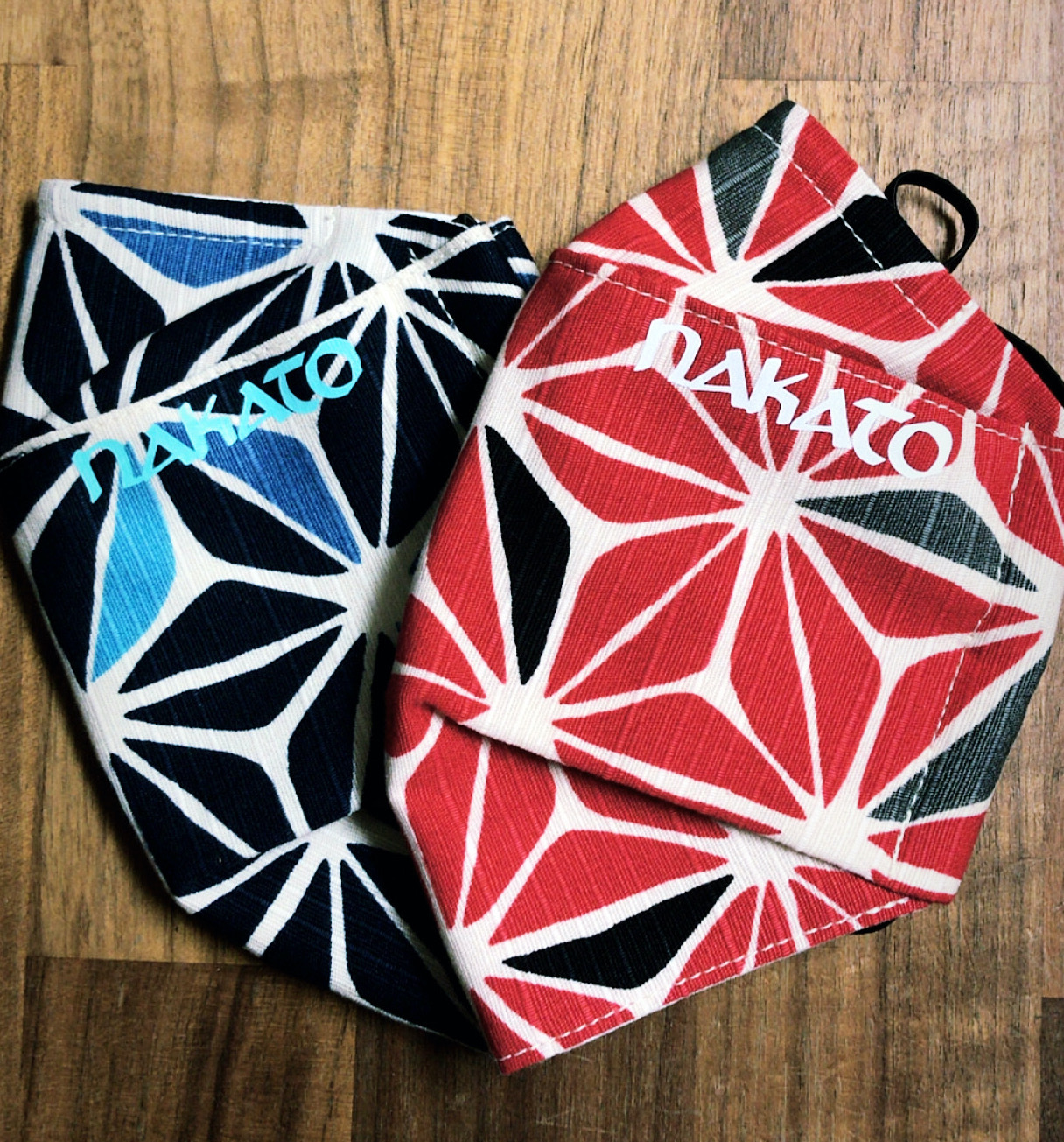 Two Japanese-inspired pattern masks in shades of red with the Nakato logo in Atlanta