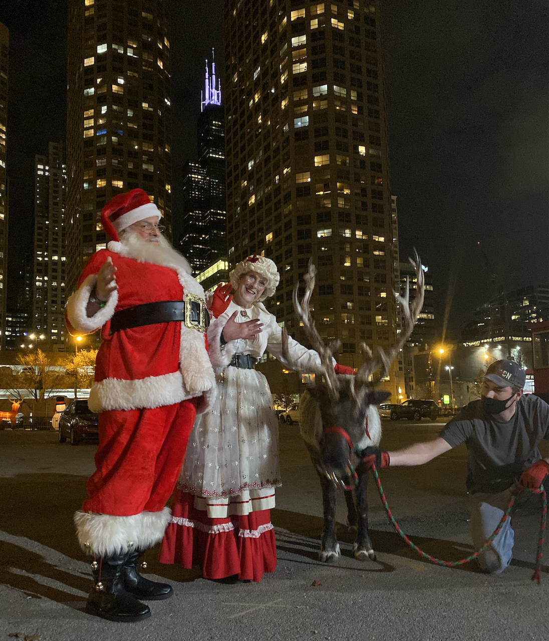 People dressed as Santa and Mrs. Clause stand in front of a downtown skyline at night.