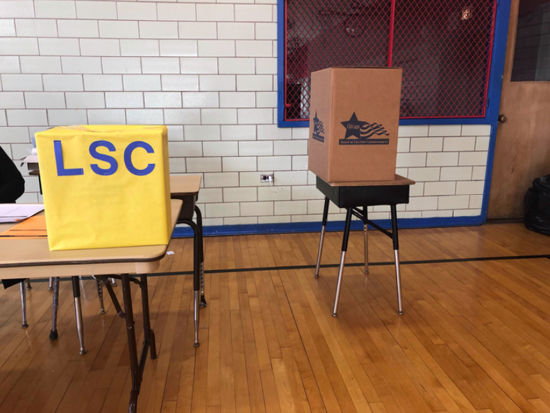 Two boxes for ballots at Yates Elementary in Chicago: The yellow box is for mail-in ballots dropped off at the campus and the brown box is for votes cast on site.