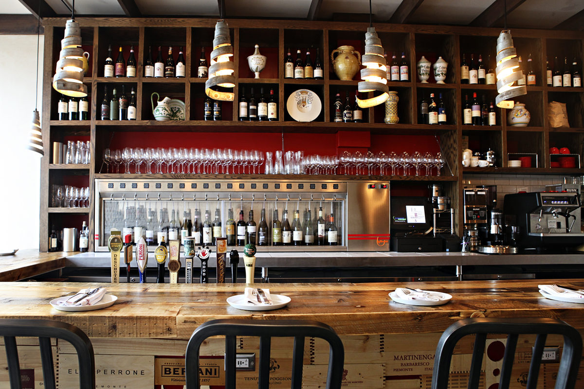 A bar stocked with tons of wine bottles, with wooden shelves and burgundy-colored paint