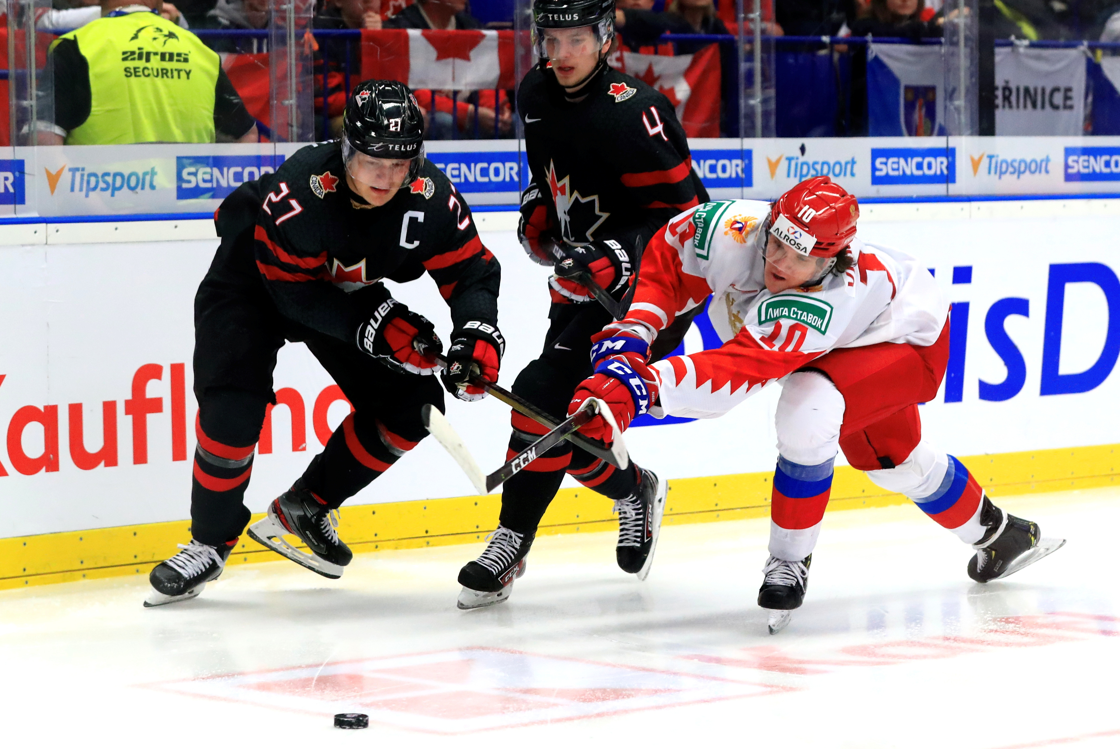 Canada's Barrett Hayton, Bowen Byram, and Russia's Dmitry Voronkov (L-R) in the 2020 World Junior Ice Hockey Championship final match between Canada and Russia at Ostravar Arena.
