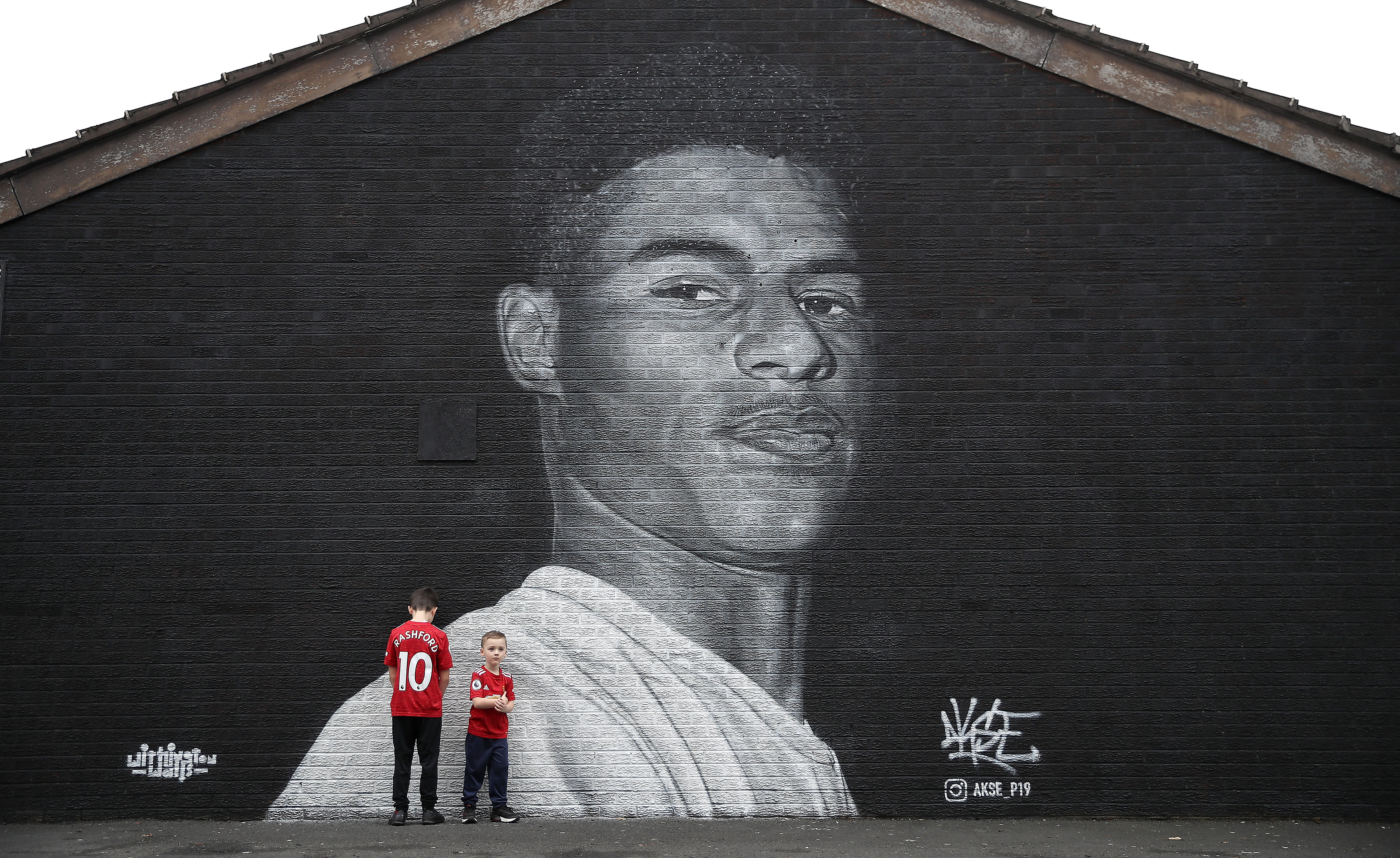Marcus Rashford Mural in Manchester with two children standing next to it