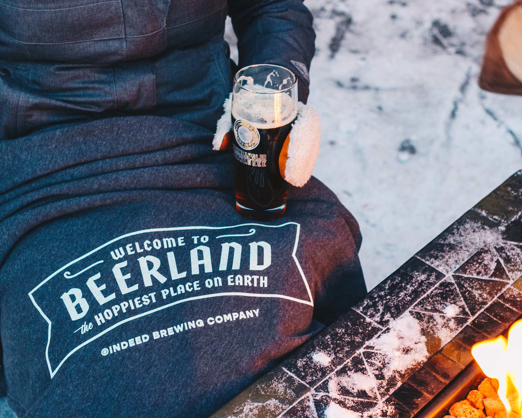 """A person sits with a """"Beerland: the hoppiest place on earth"""" t-shirt over their lap. A beer in a mittened hand, and a firepit is visible at the edge of the image."""