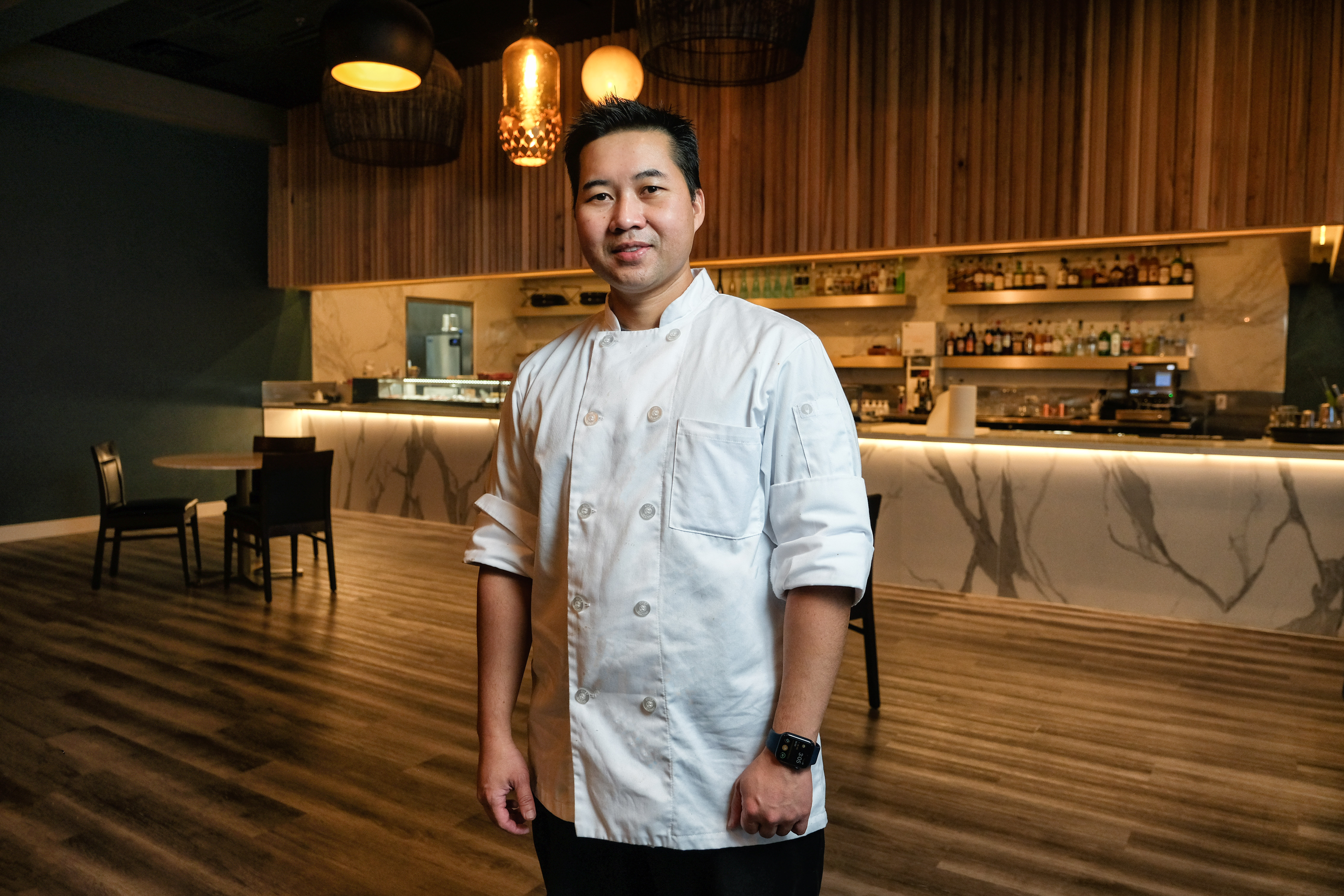 A chef stands in a dining room Robata En
