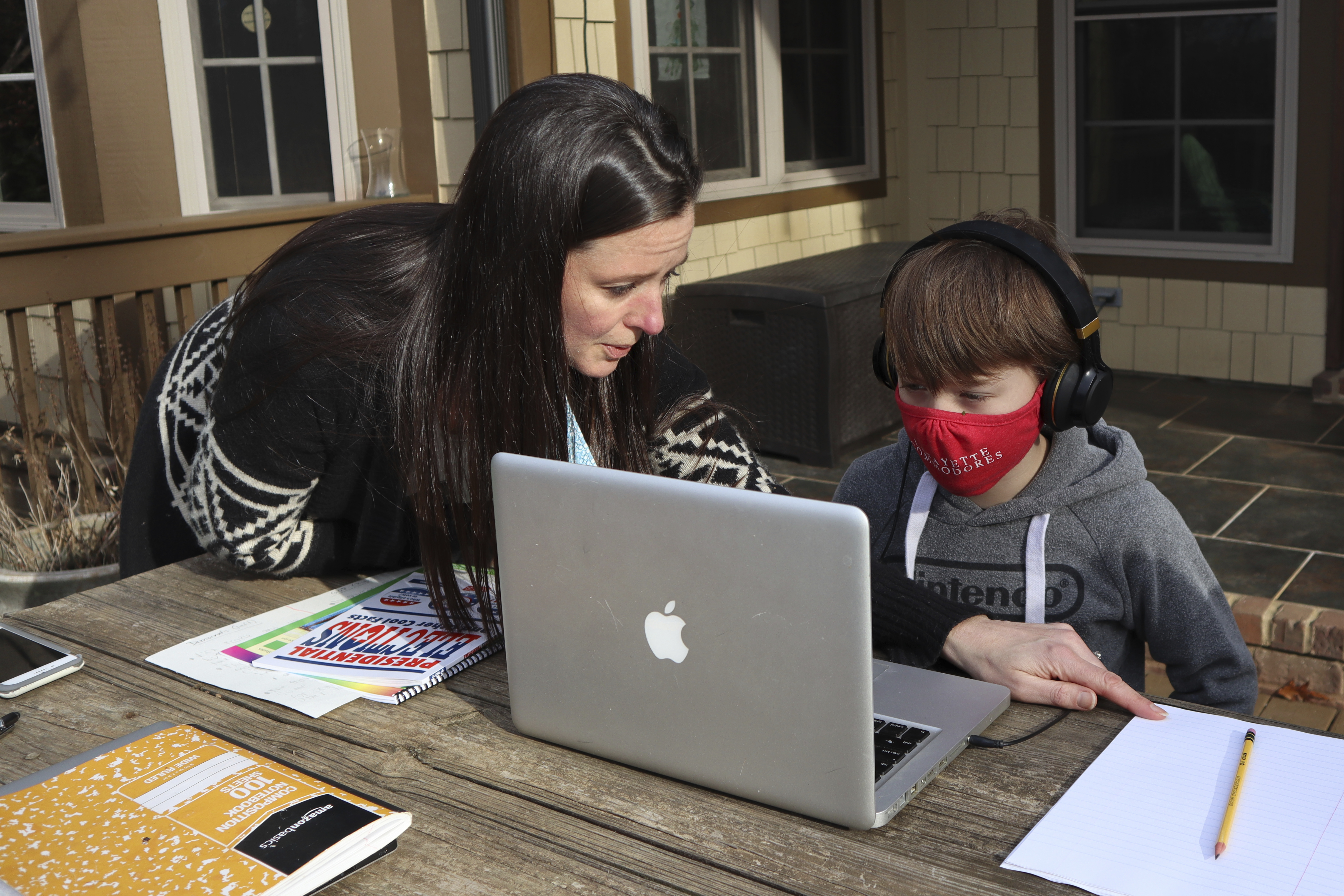 Angela Atkins helps her son Jess Atkins work on a math problem on his laptop during home schooling.