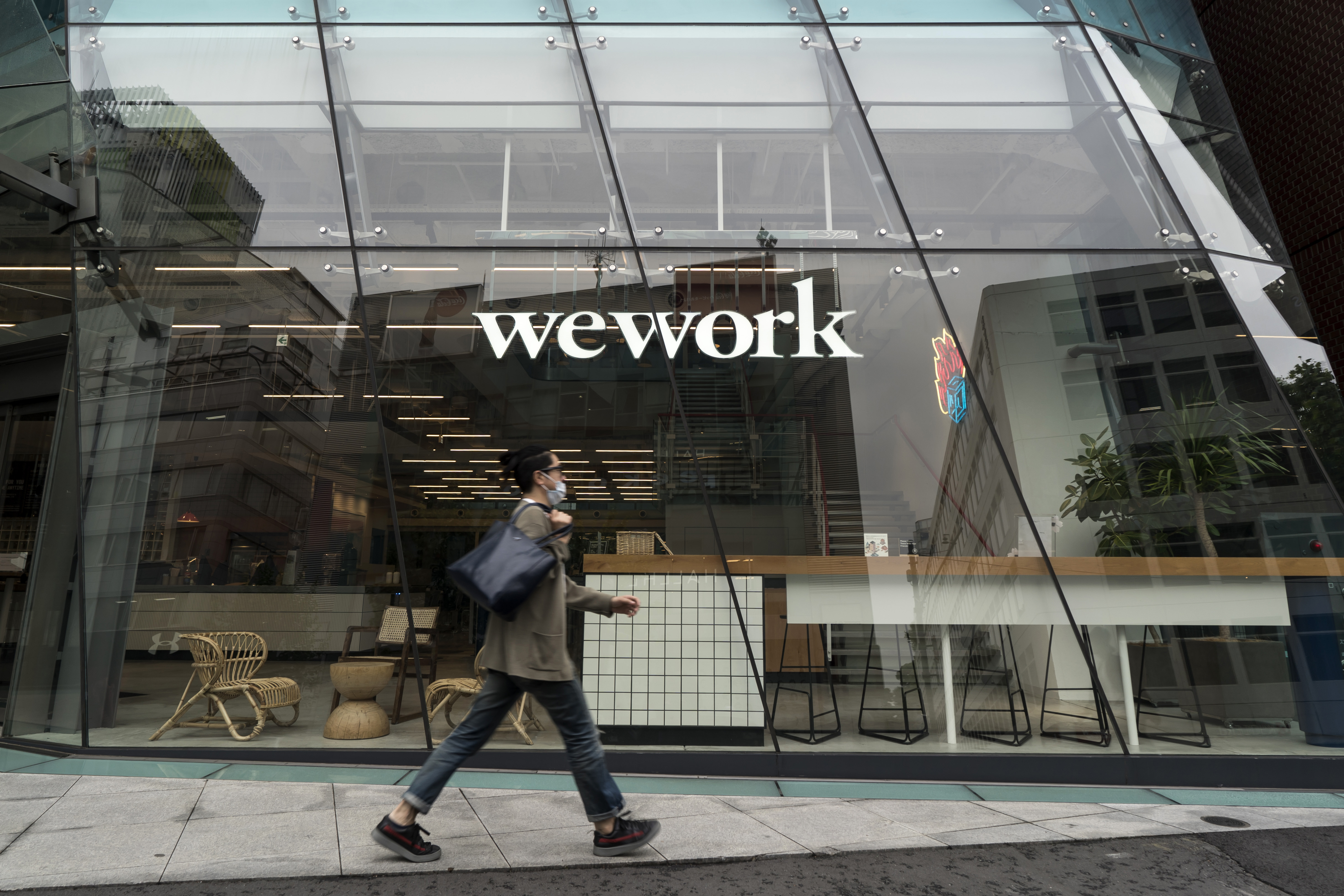 A man wearing a mask walks in front of a WeWork building.