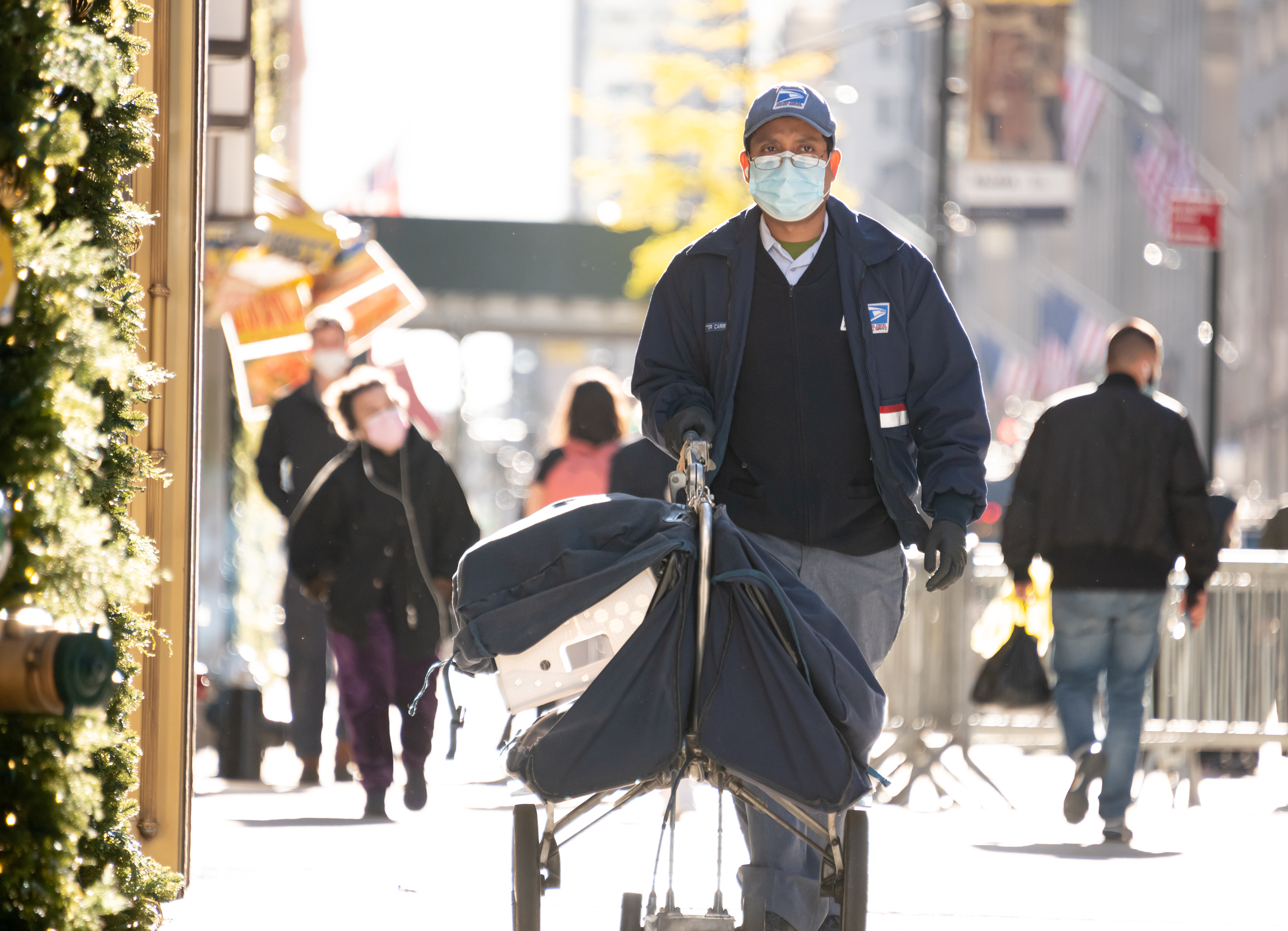 A USPS worker walks down the street with rolling parcel bags, wearing a mask.