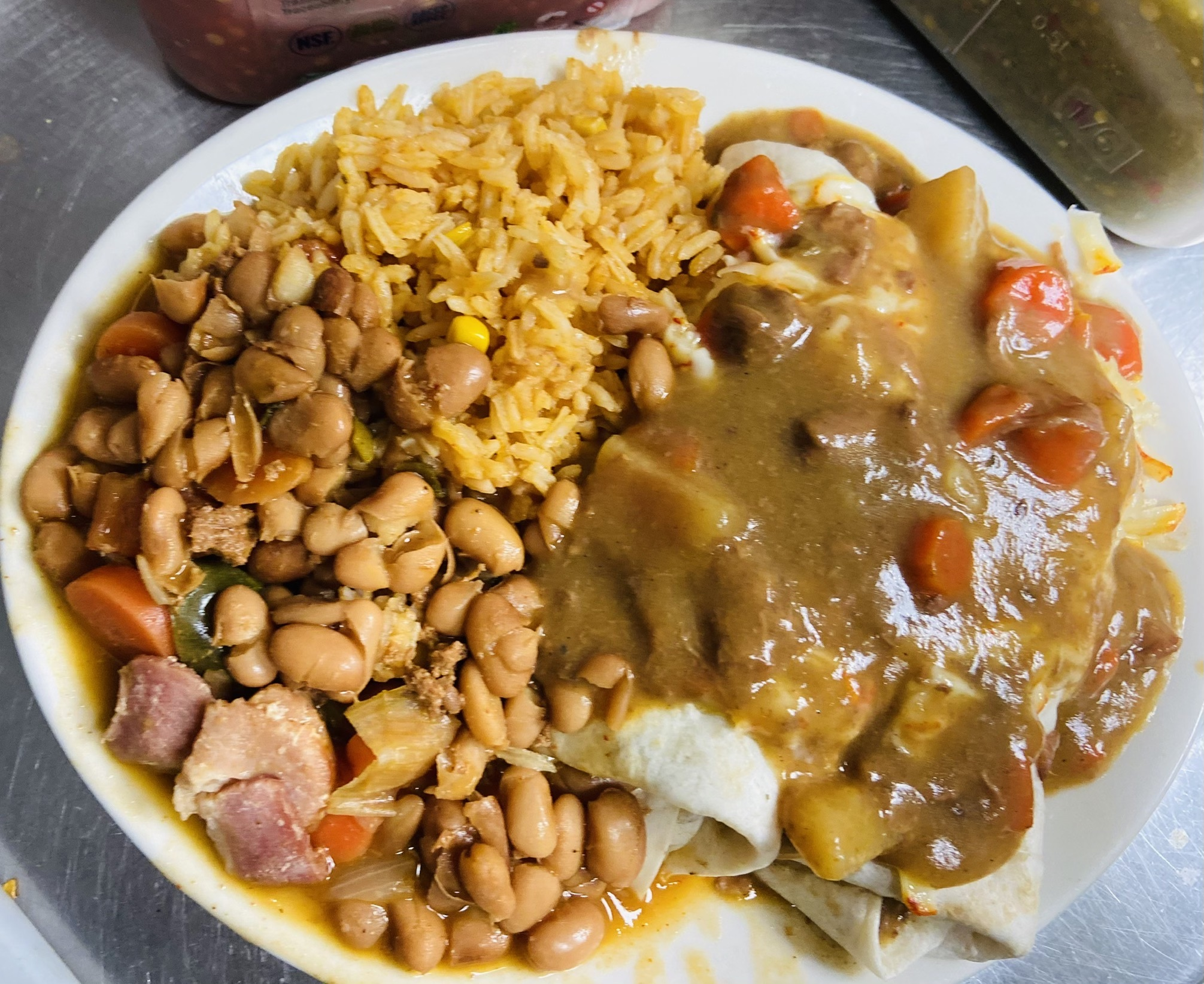 A plate with burritos covered in a brown sauce, sides of pinto beans, and rice.
