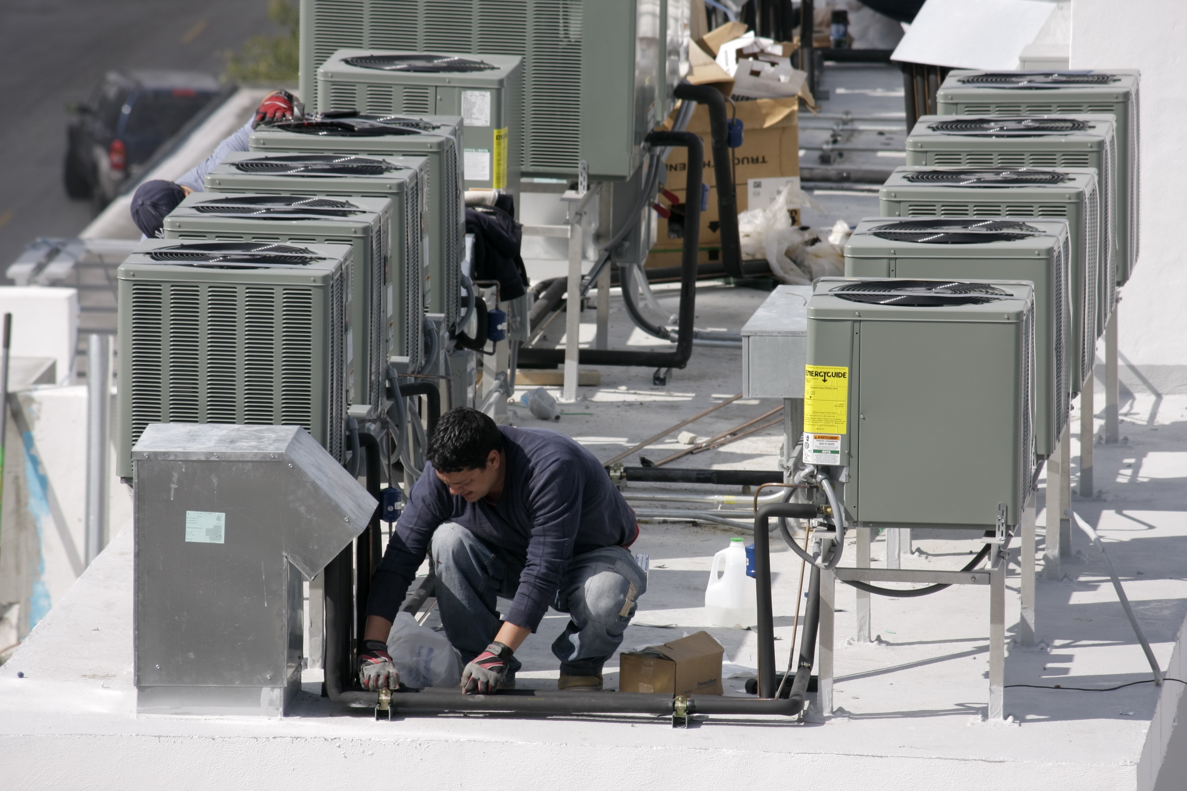 A worker on a rooftop installing air conditioning at a hotel on Ocean Drive